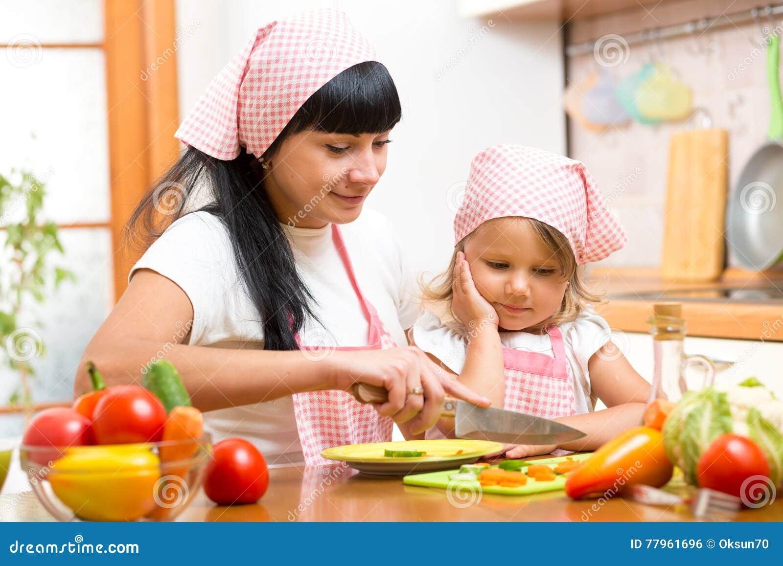 Enfant de enseignement de mère faisant la salade dans la cuisine Maman et enfant coupant le légume sur la planche à découper avec