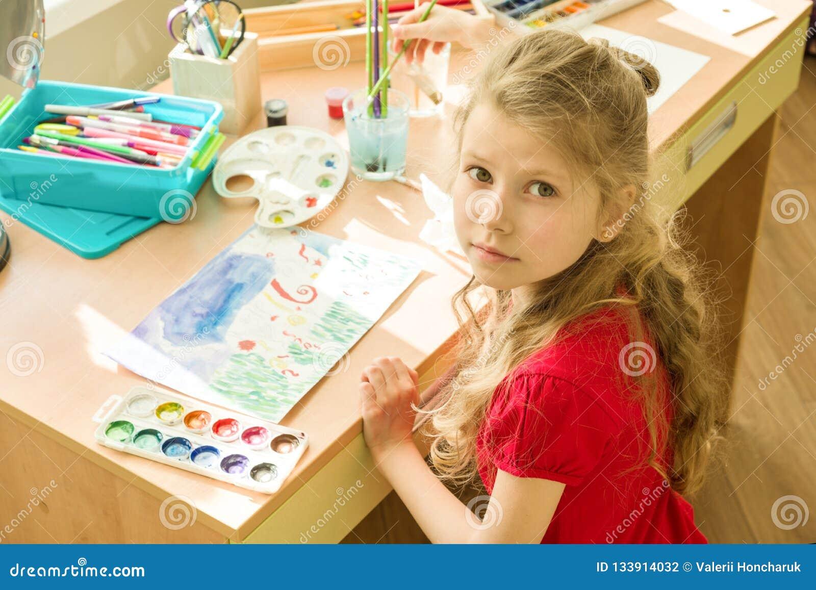 Enfant de fille 7 années, aquarelle de dessin à la table à la maison Créativité d enfant, récréation, développement
