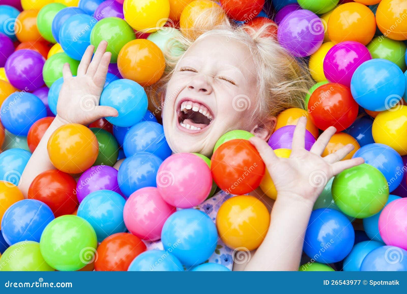 Enfant de fille ayant l amusement jouer dans les billes colorées
