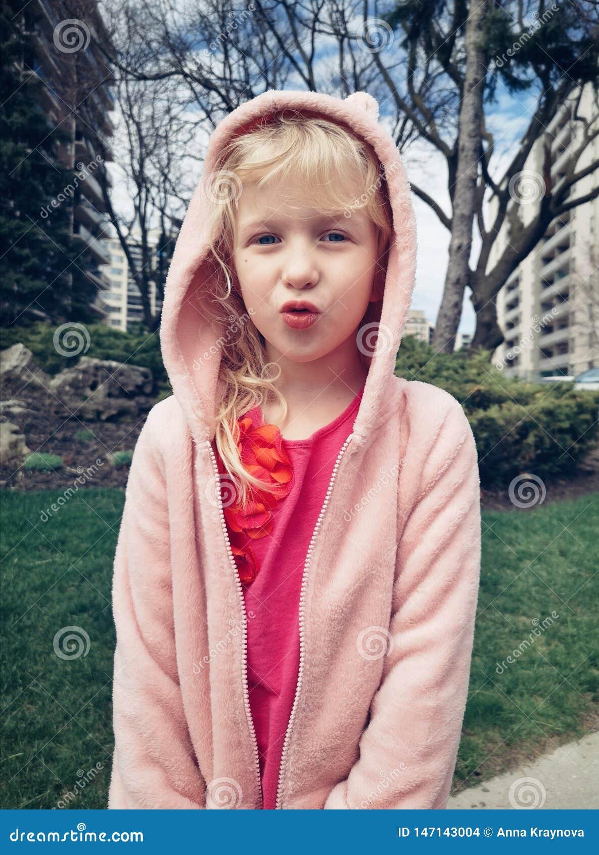 Enfant de fille faisant les visages idiots drôles avec des lèvres de canard