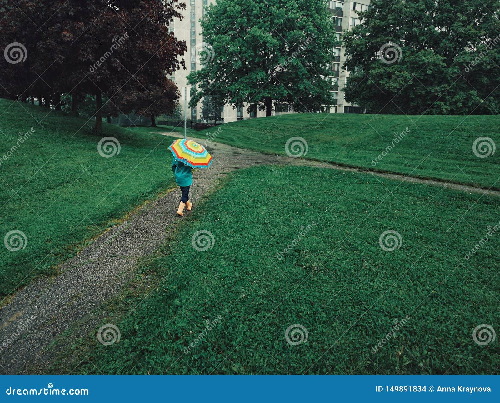Enfant de fille marchant sur la route de rue sous la pluie avec le parapluie d arc-en-ciel