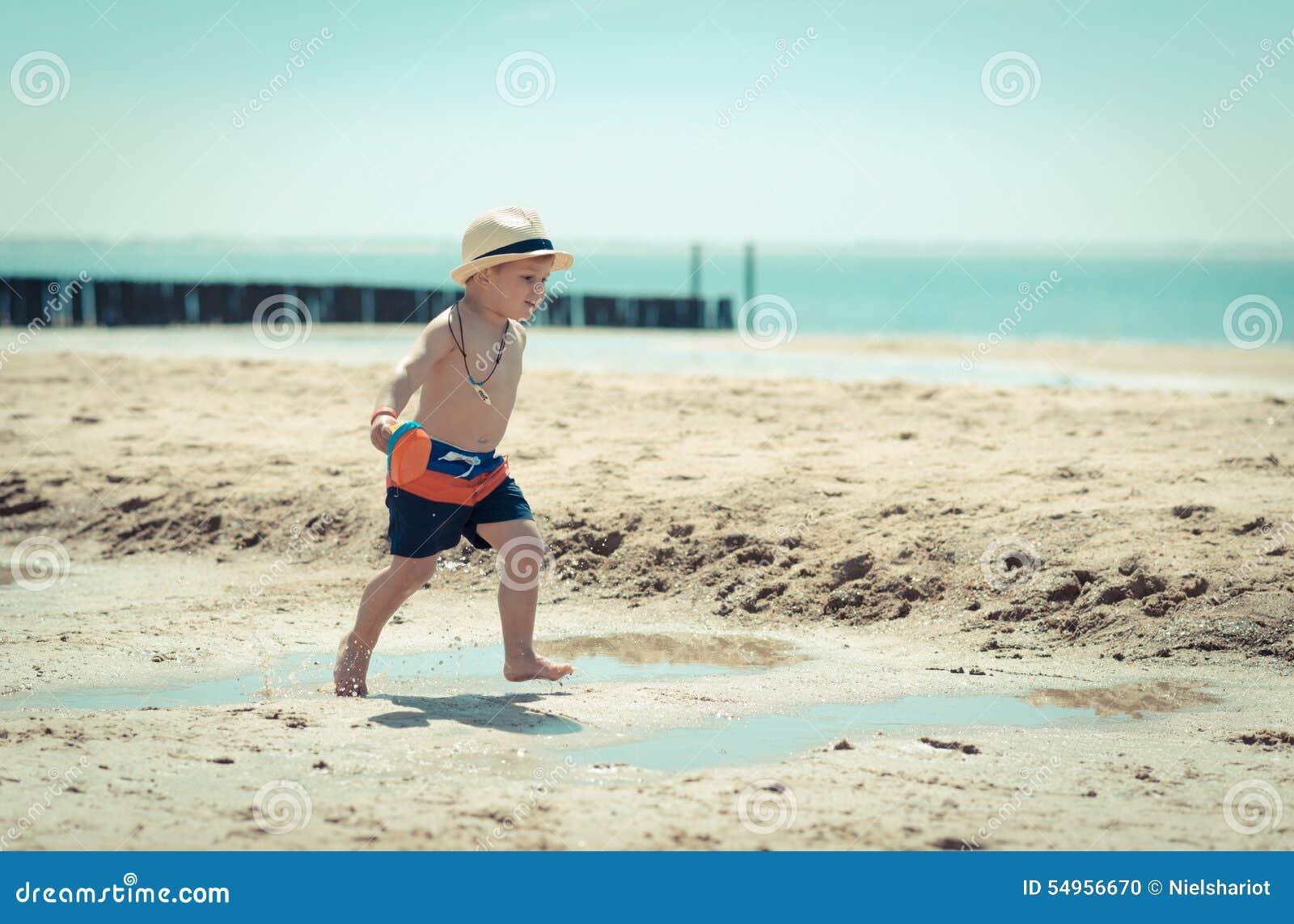Enfant de petit garçon marchant sur la plage inspectant une coquille