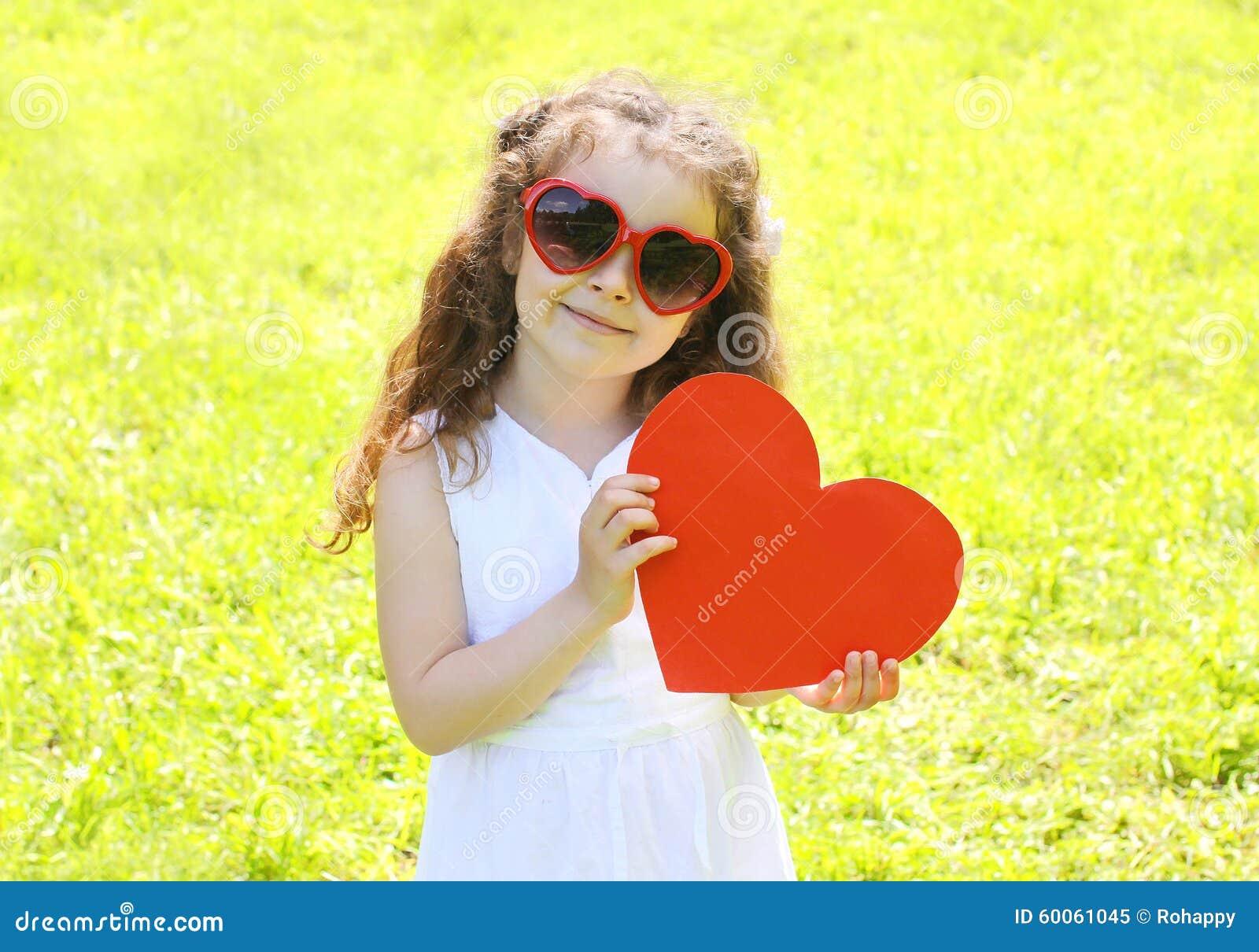 6c5527f2476551 Enfant de petite fille dans des lunettes de soleil avec le grand coeur de  papier rouge