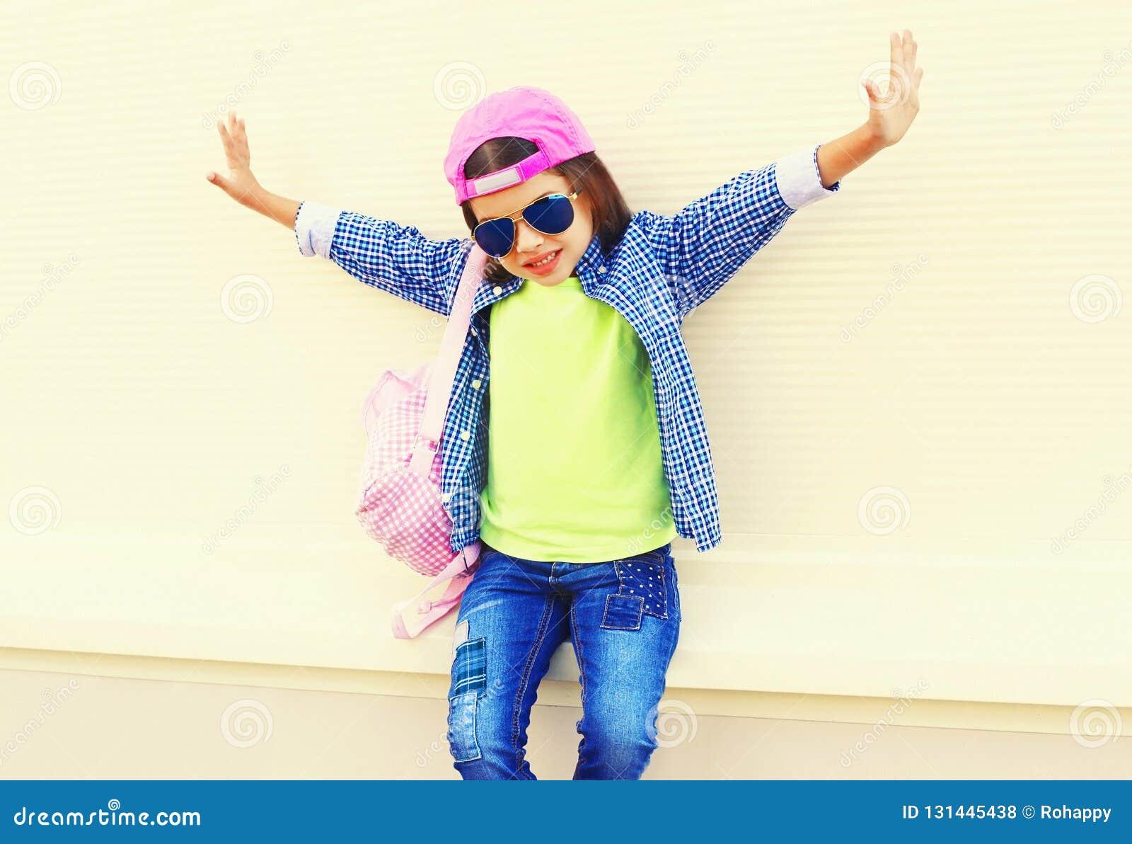 Enfant de petite fille de mode dans la casquette de baseball ayant l amusement dans la ville sur le blanc