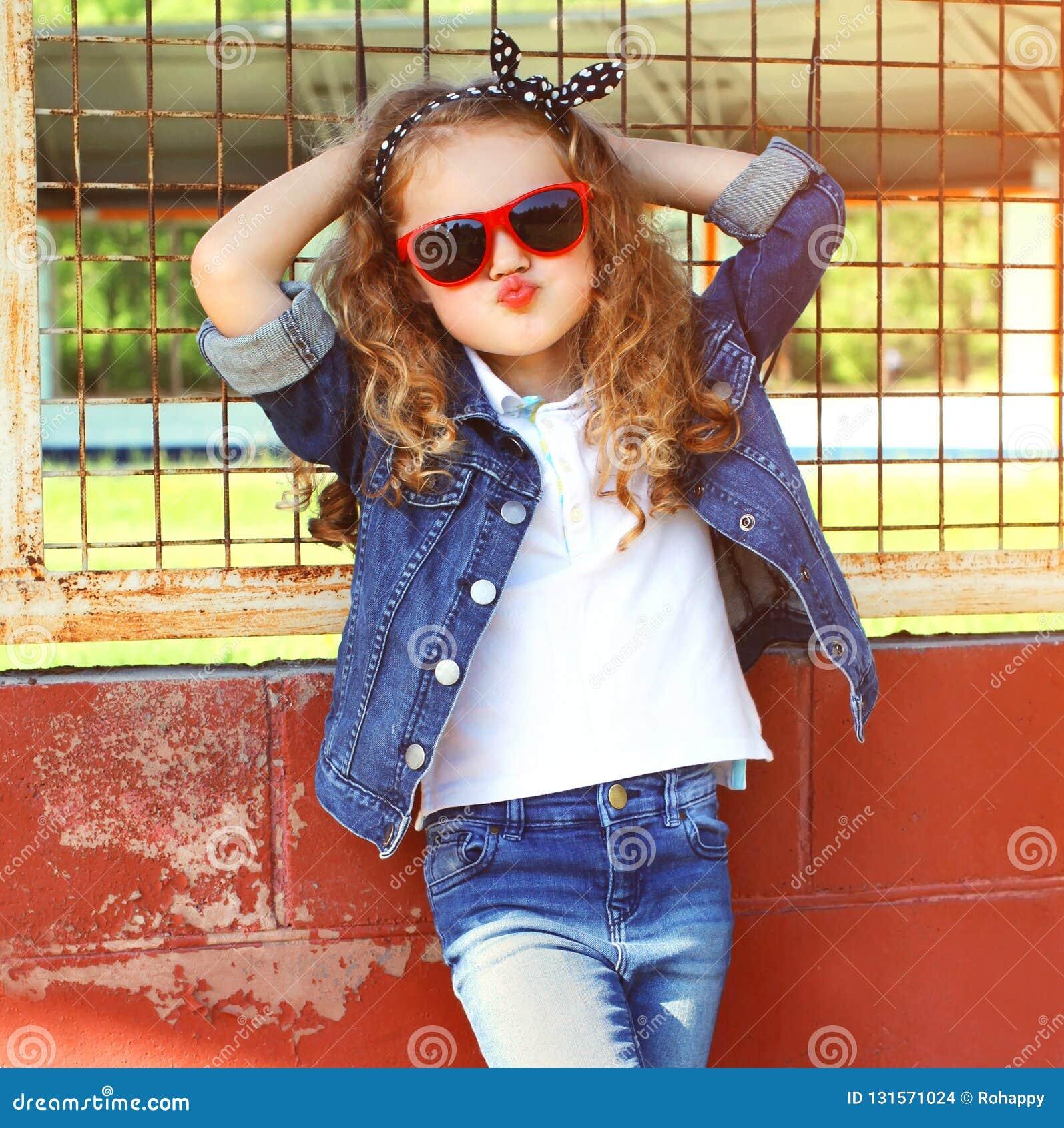 Enfant de petite fille de portrait de mode dans la veste de jeans, pose rouge de lunettes de soleil