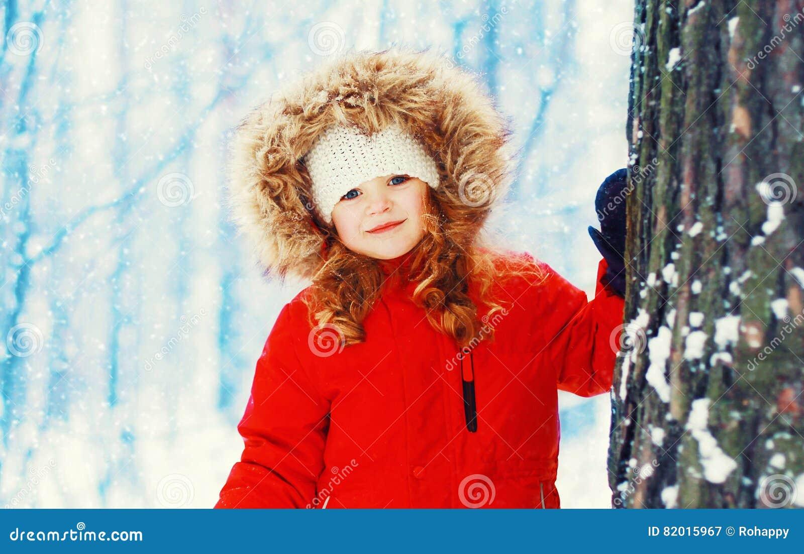 Enfant de sourire heureux de petite fille de portrait d hiver près d arbre au-dessus de neigeux