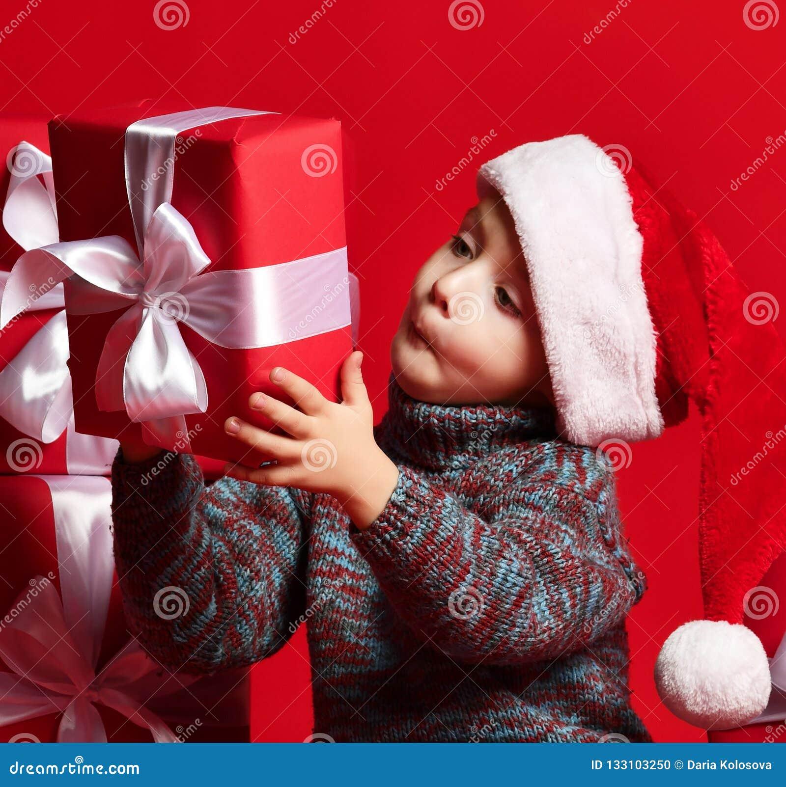 Enfant drôle de sourire dans le chapeau rouge de Santa jugeant le cadeau de Noël disponible Concept de Noël