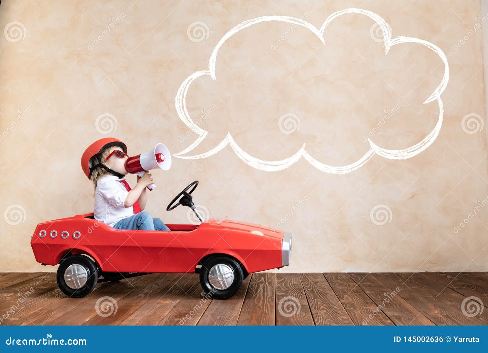 Enfant dr?le conduisant la voiture de jouet ? la maison