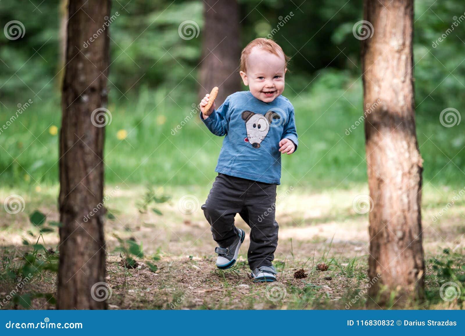 Enfant en bas âge de sourire heureux dans la forêt