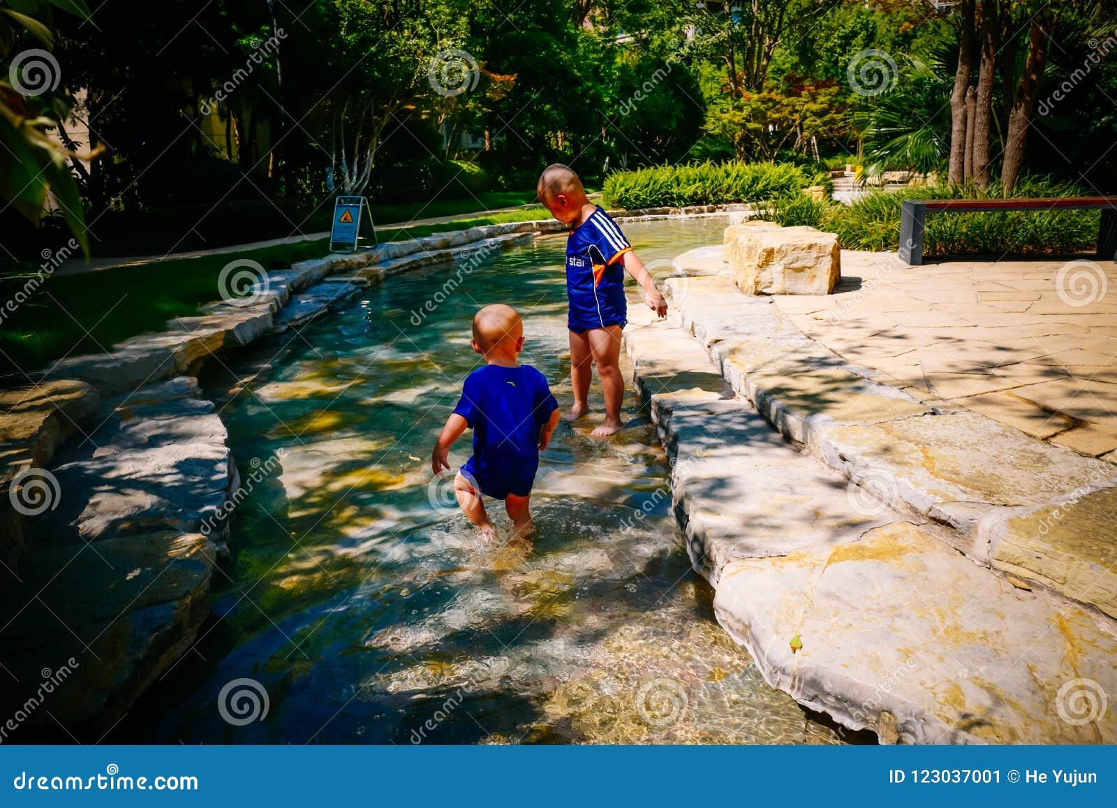 Enfant en bas âge jouant dehors en rivière