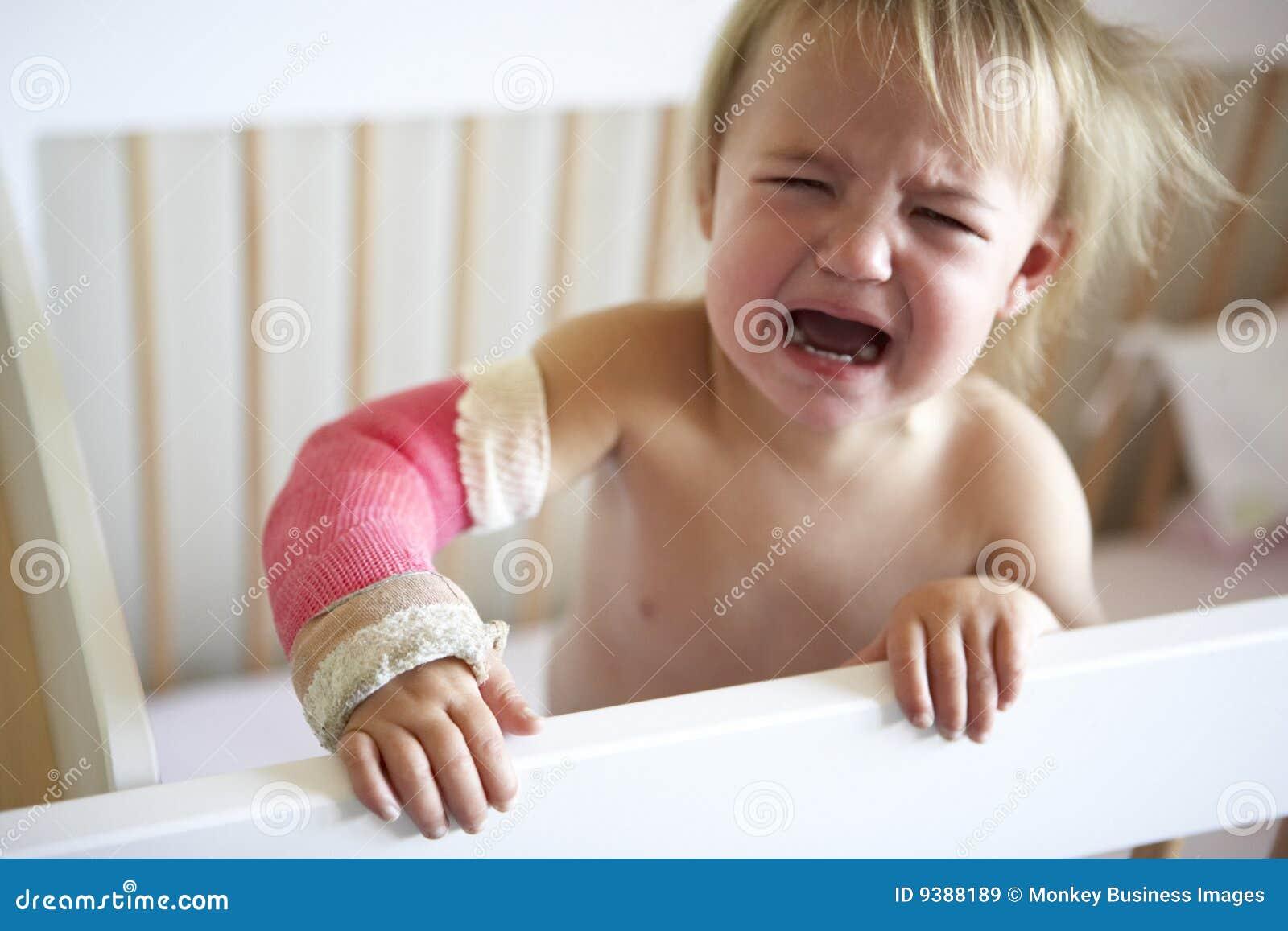Enfant en bas âge pleurant avec le bras dans le moulage