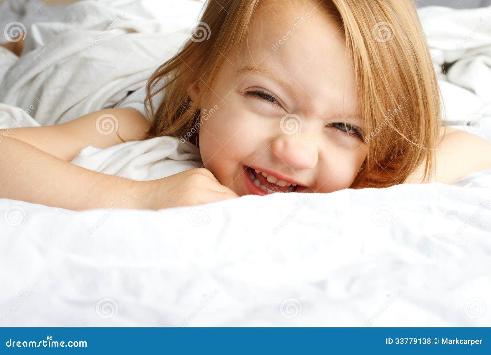 Enfant en bas âge souriant dans des couvertures blanches