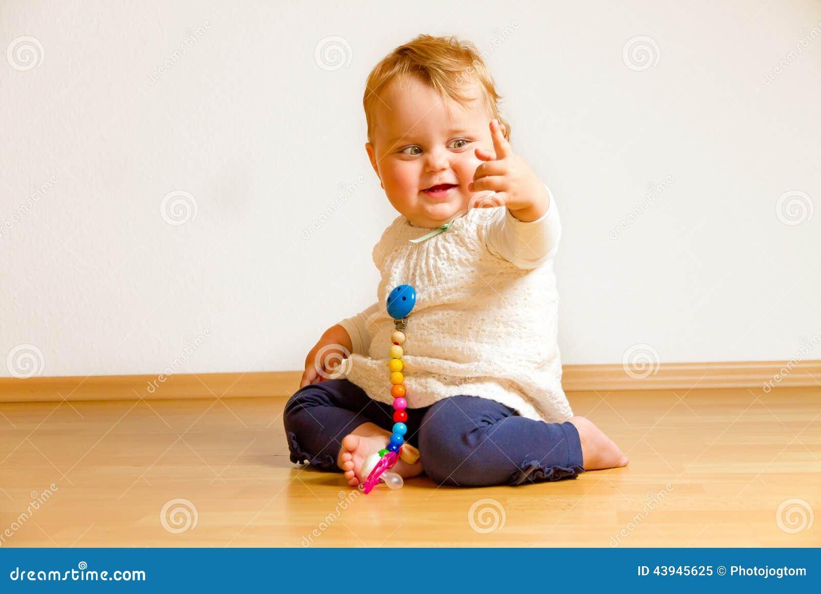 Enfant en bas âge sur un plancher de parquet