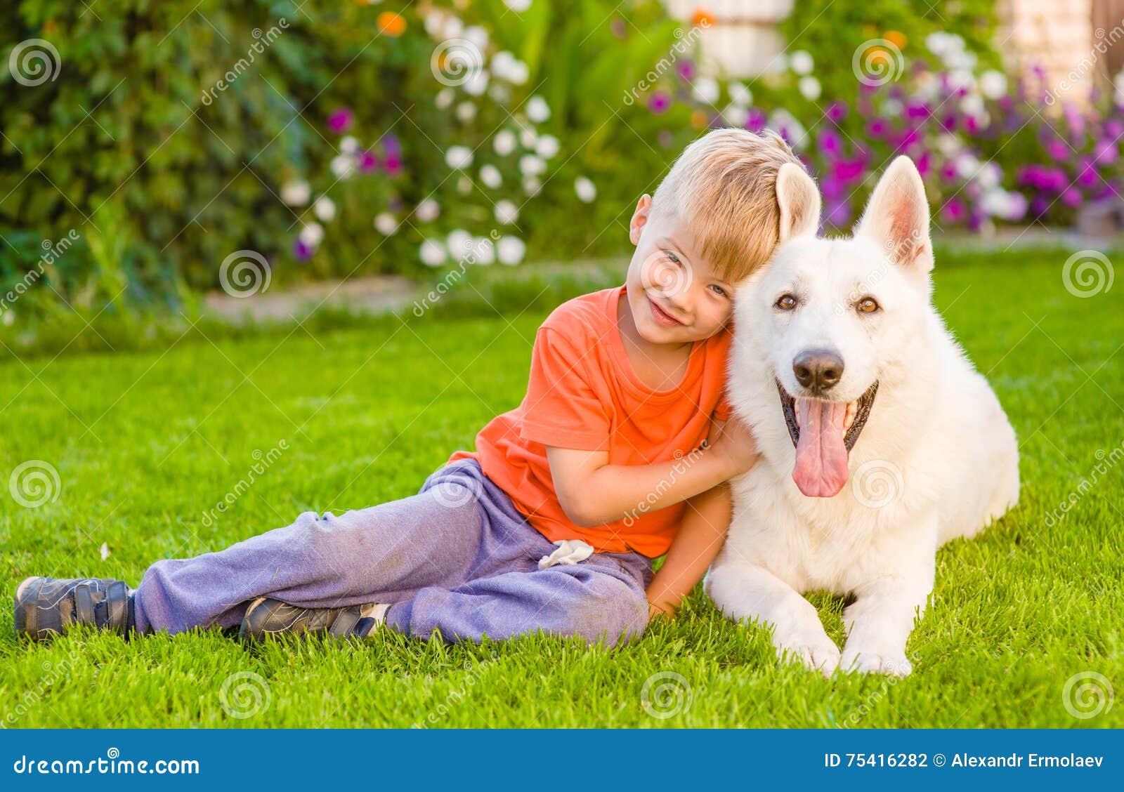 enfant et chien de berger suisse blanc ensemble sur l 39 herbe verte photo stock image du hound. Black Bedroom Furniture Sets. Home Design Ideas