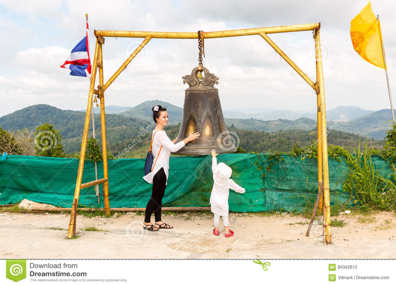 Enfant et maman près de gong thaïlandais à Phuket Cloche asiatique de tradition dans le temple de bouddhisme en Thaïlande Grand s