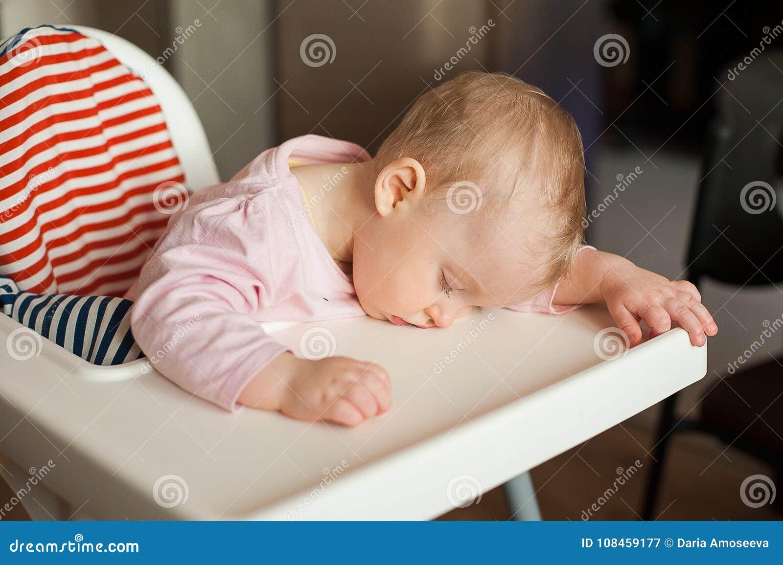 Enfant fatigué dormant dans le highchair après le déjeuner Bébé mignon girllying son visage sur le plateau de table