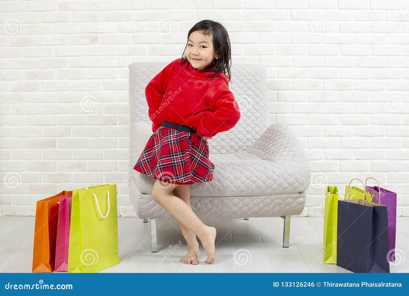 Enfant heureux avec des sacs à provisions Sourire de fille d achats Bel a