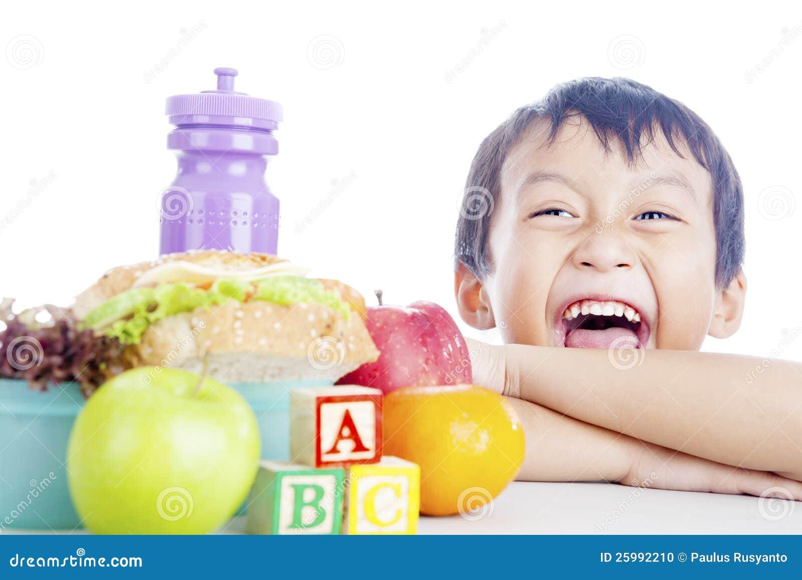 Enfant heureux avec le repas scolaire