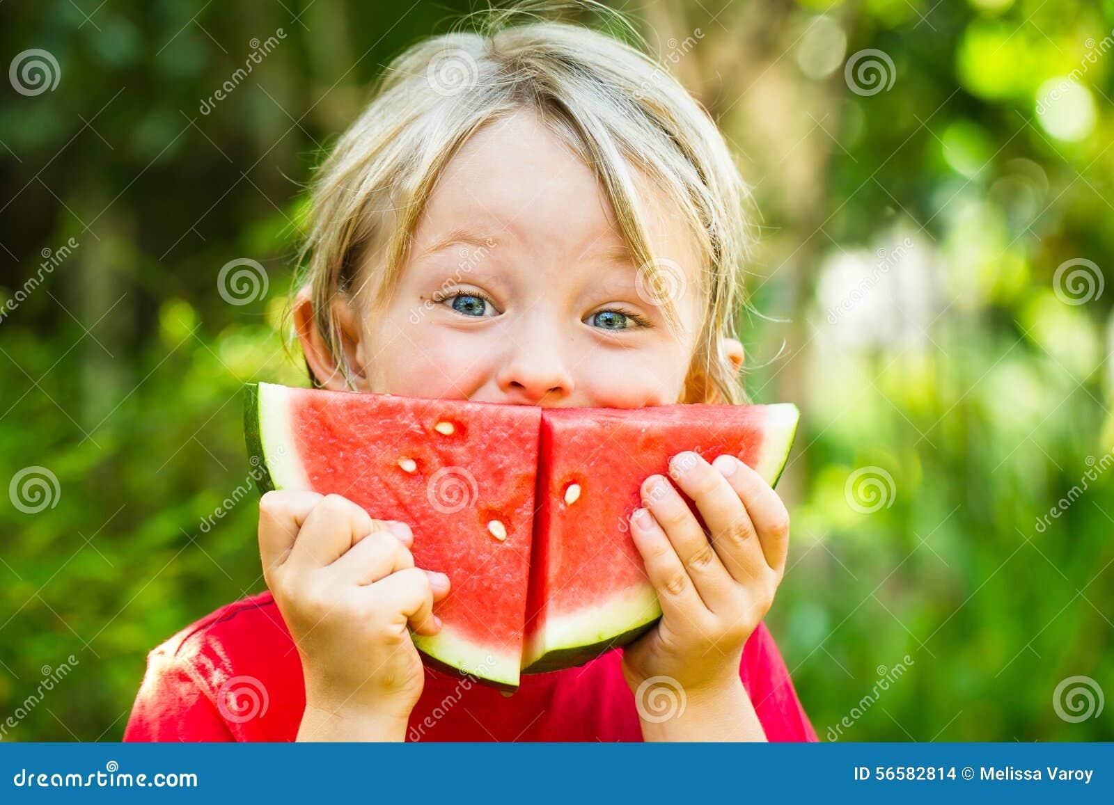 Enfant heureux drôle mangeant la pastèque dehors