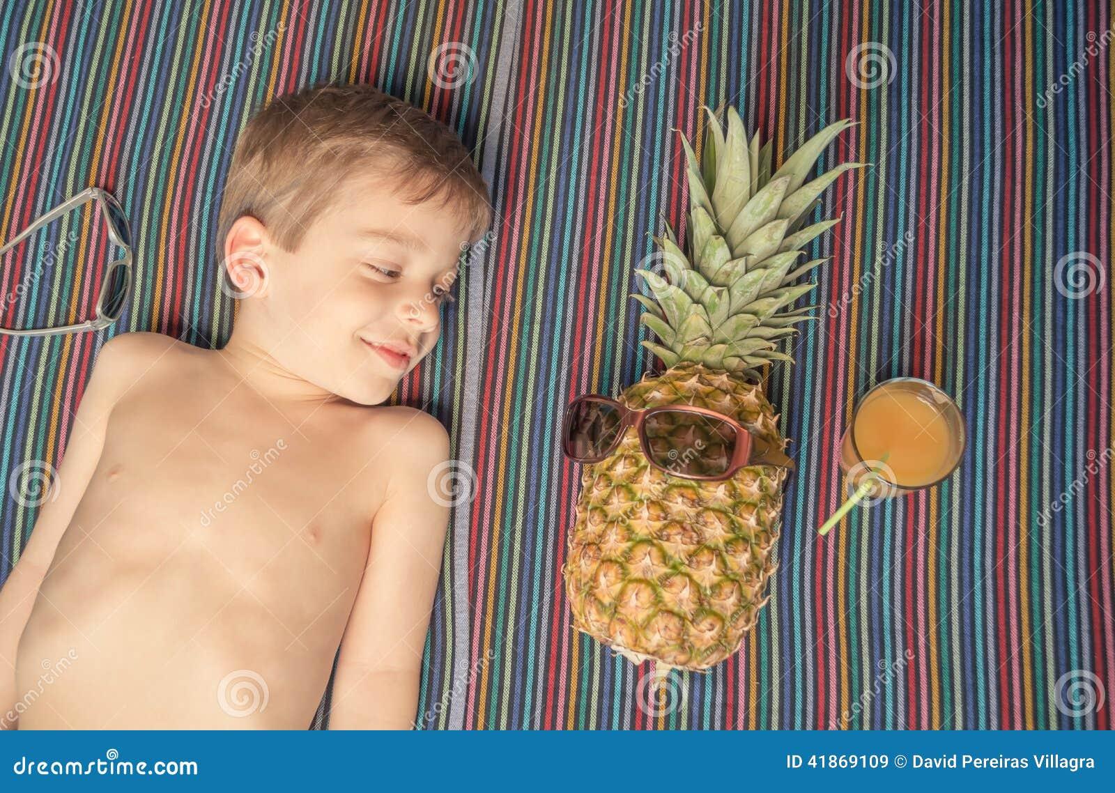 enfant heureux et ananas prenant un bain de soleil au. Black Bedroom Furniture Sets. Home Design Ideas