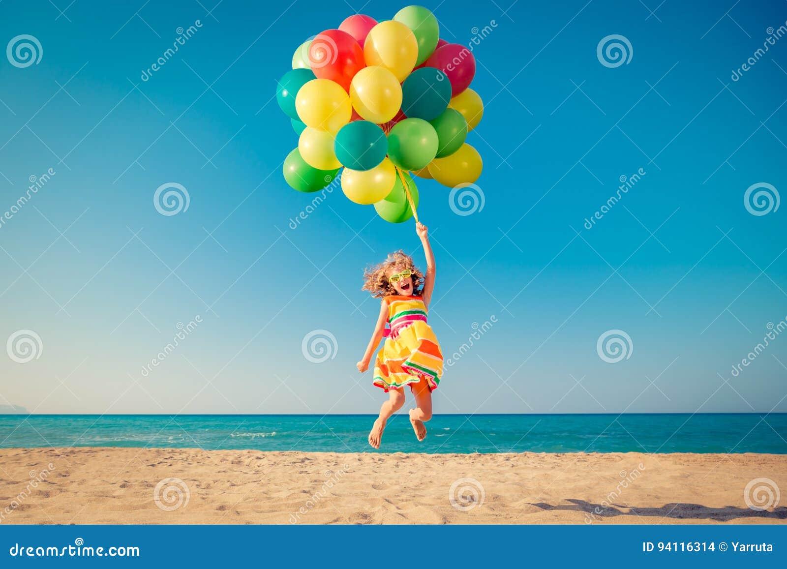 Enfant heureux sautant avec les ballons colorés sur la plage sablonneuse