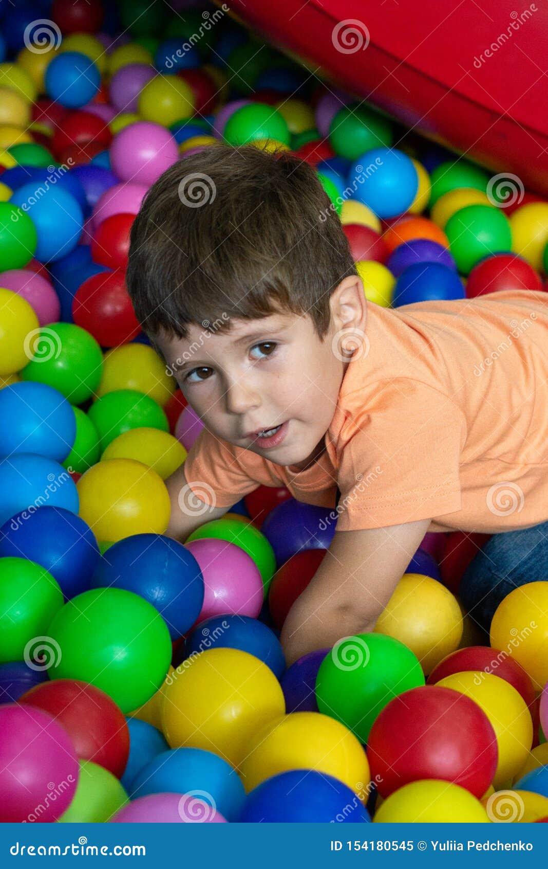 Enfant jouant avec les boules color?es dans la piscine de boule de terrain de jeu Jouets d activit? pour peu d enfant Émotion de