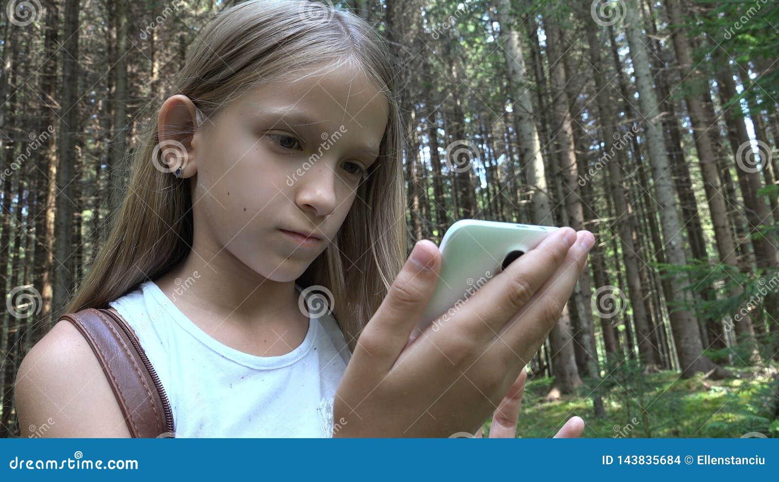 Enfant jouant la Tablette ext?rieure dans le camping, utilisation Smartphone d enfant dans la for?t, vue de fille