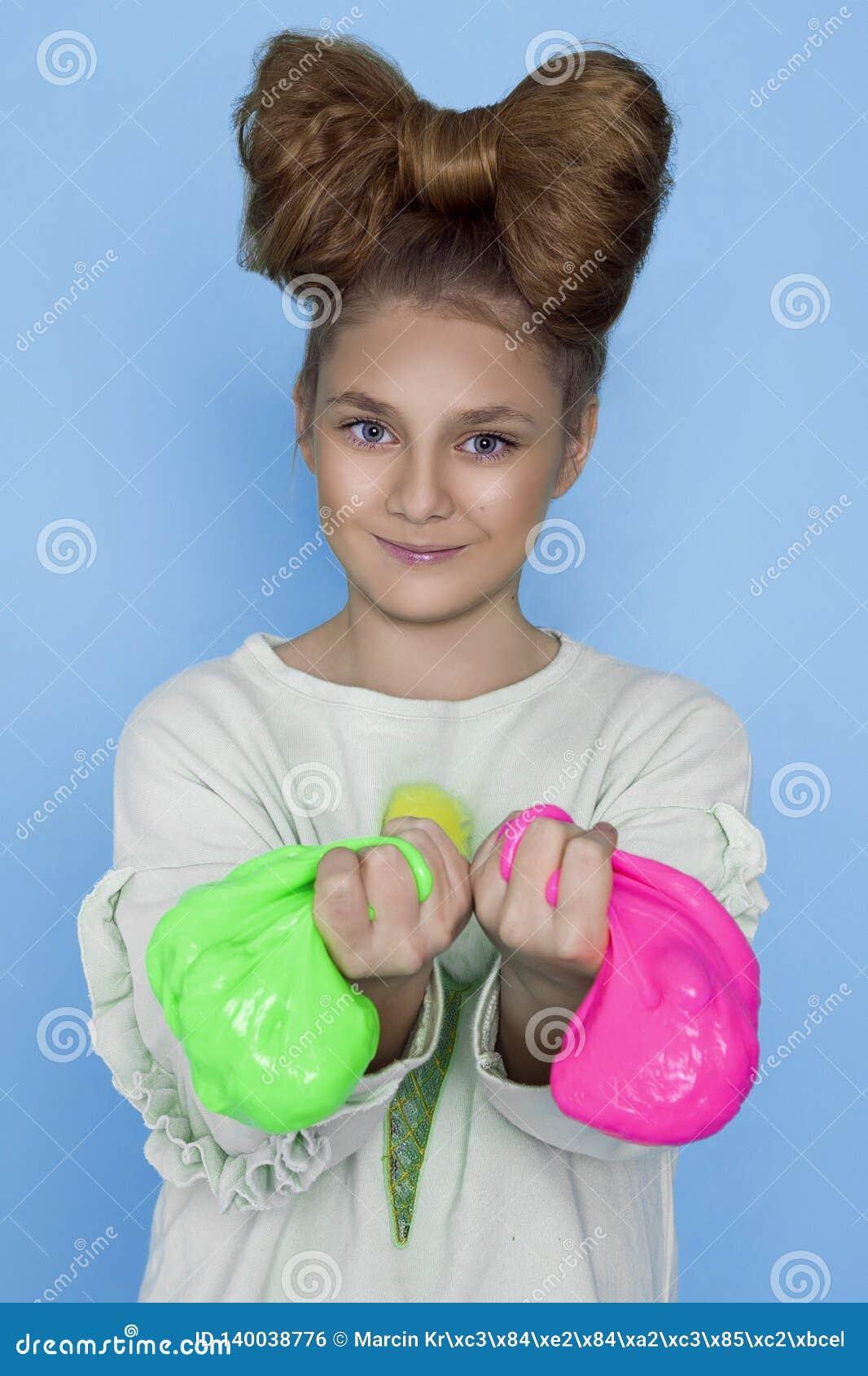 Enfant jouant Toy Called Slime fabriqué à la main, compression de mains d isolement sur le fond bleu