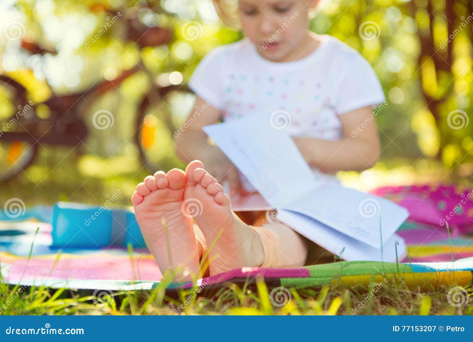 Enfant mignon s asseyant sur l herbe avec le livre Paye au foyer