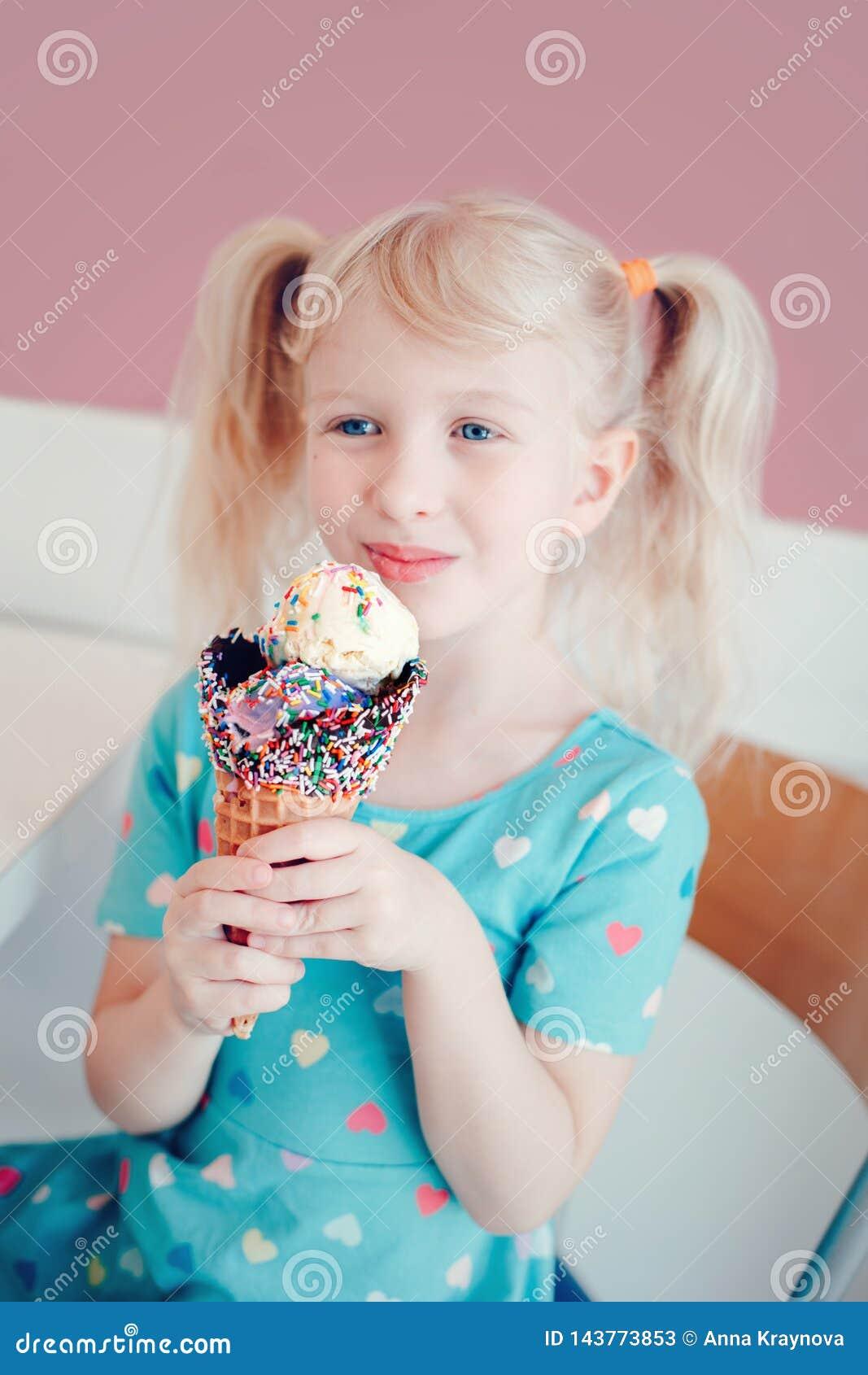 Enfant pr?scolaire blond caucasien de fille avec des yeux bleus tenant la cr?me glac?e dans le grand c?ne de gaufre