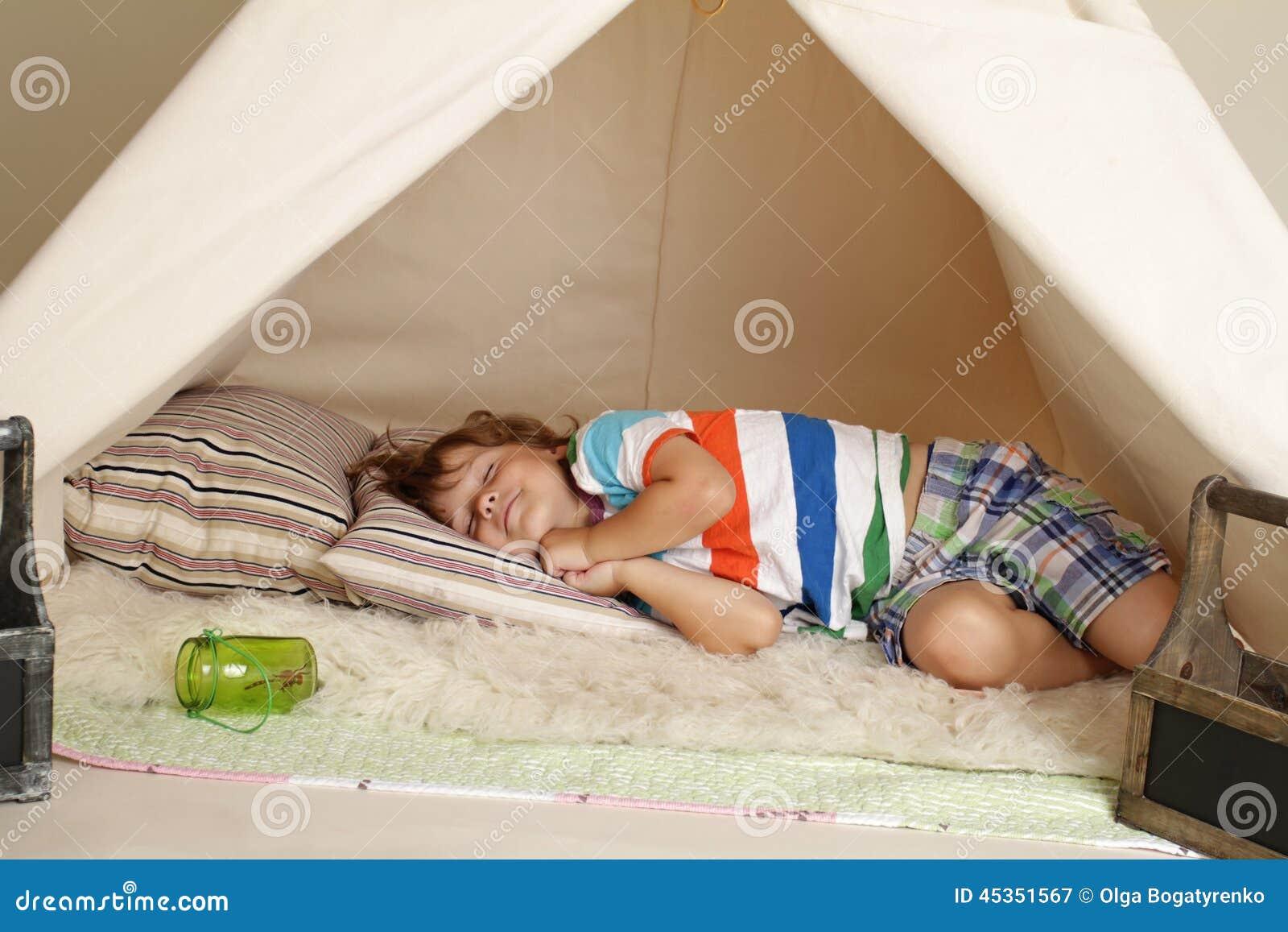Enfant prenant un petit somme dans une tente de tipi