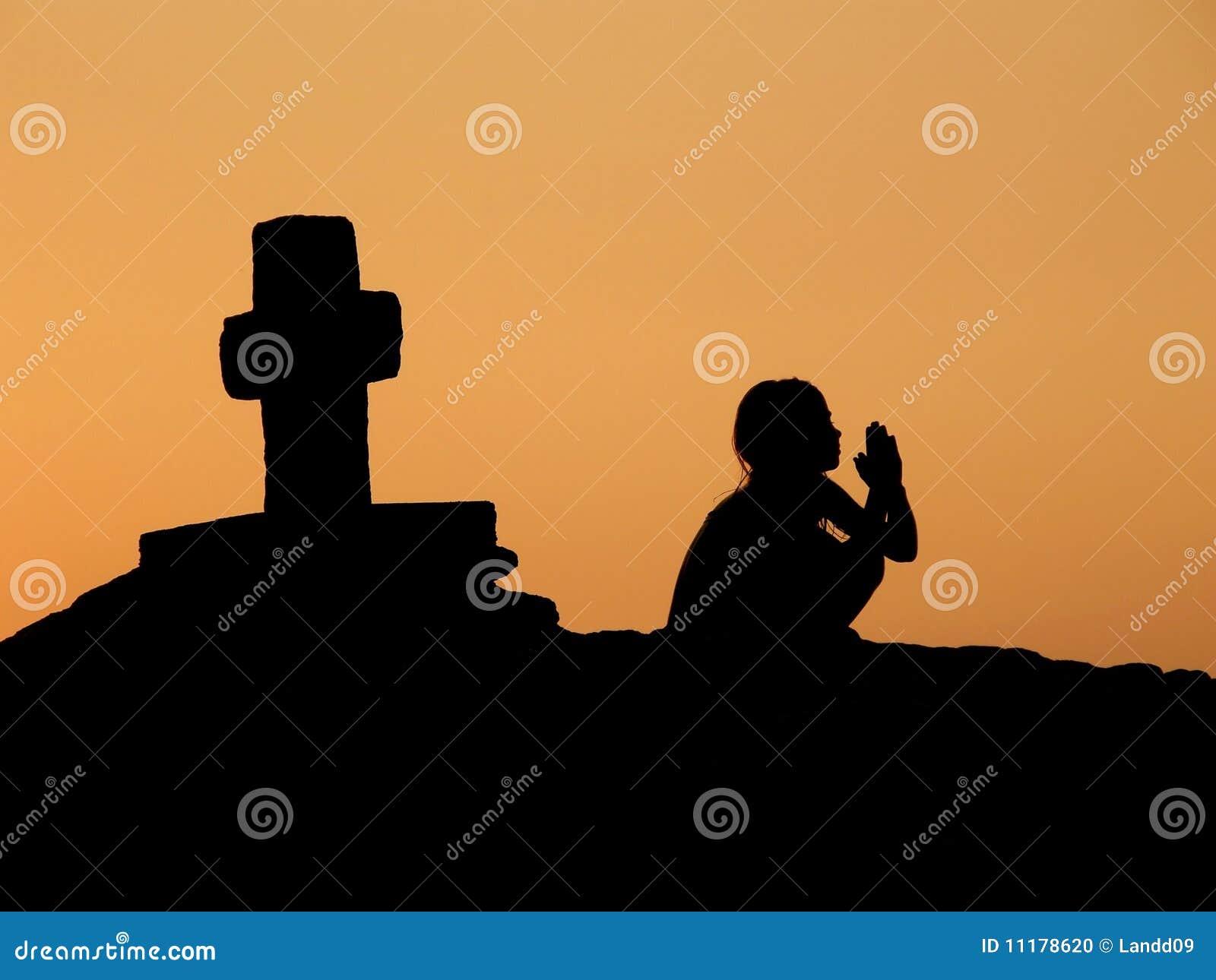 Enfant, prière, croix dans le coucher du soleil