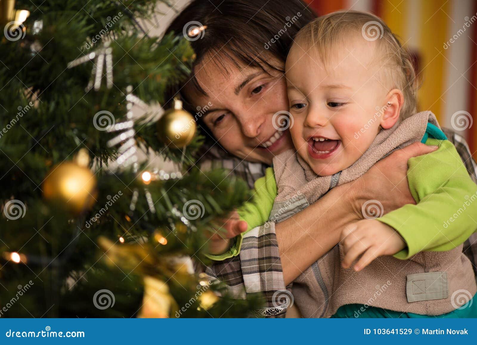 Enfant riant mignon dans des bras de sa mère