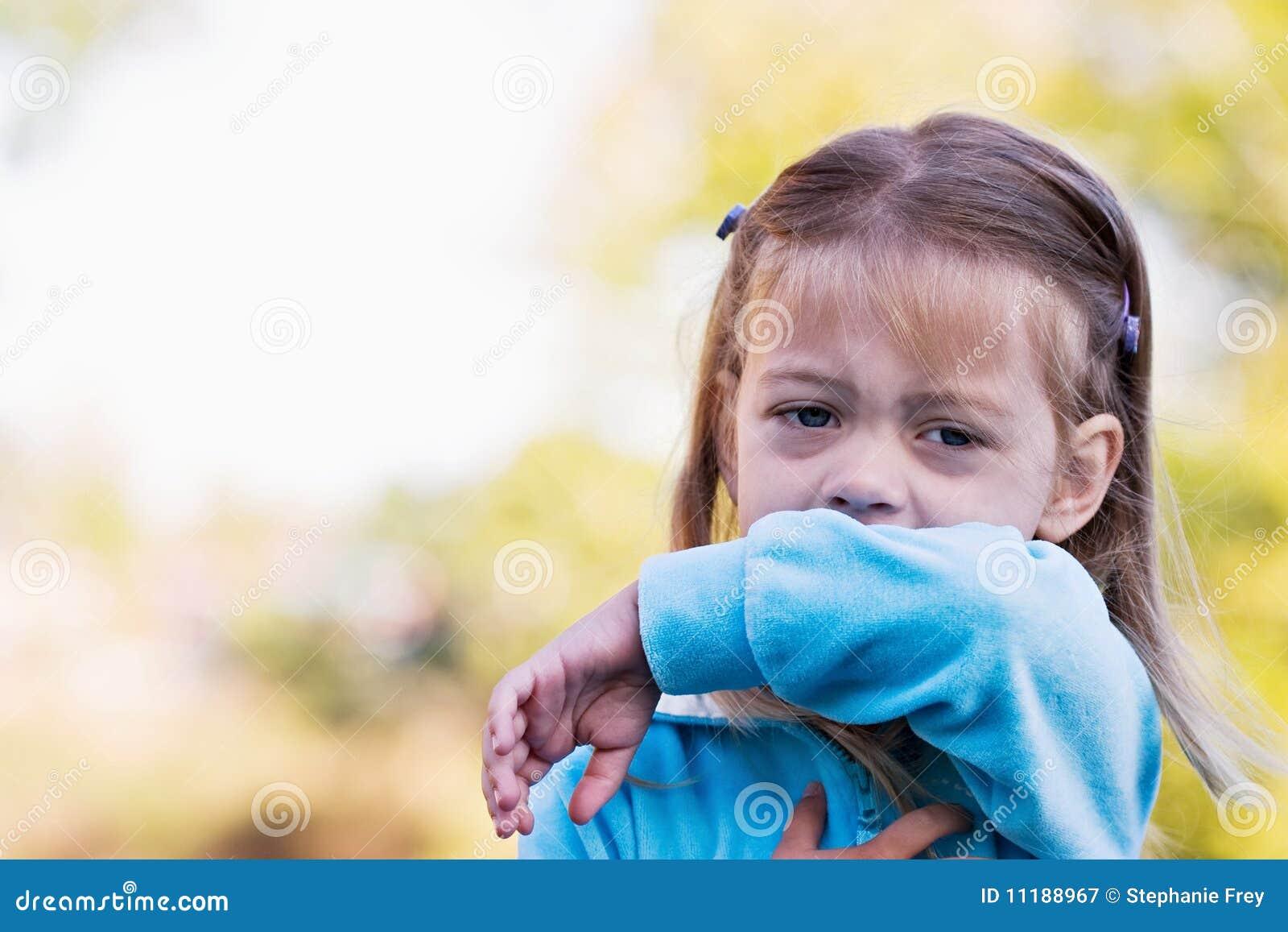 Enfant toussant ou éternuant dans le bras
