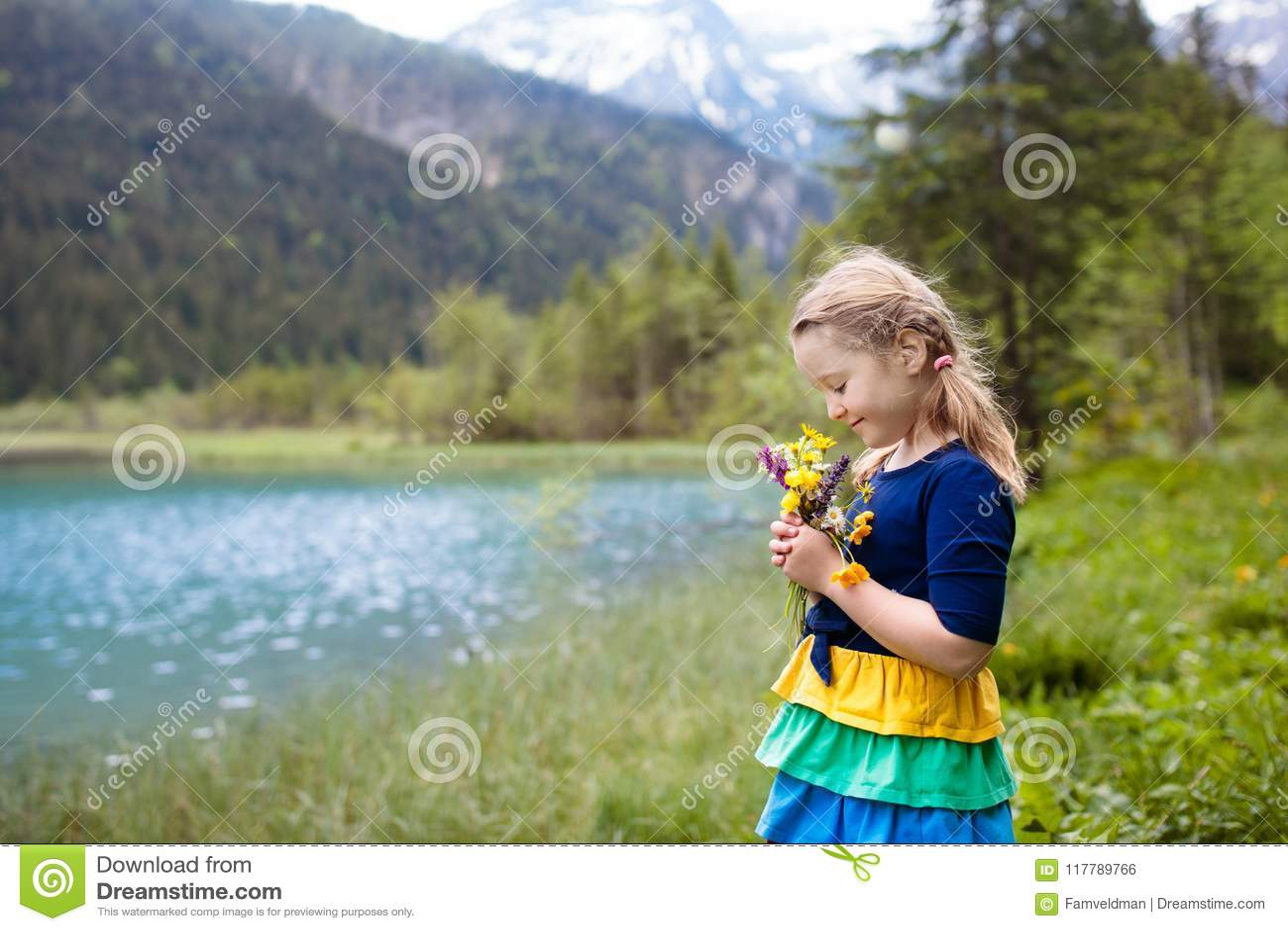 Enfant trimardant dans le domaine de fleur au lac de montagne
