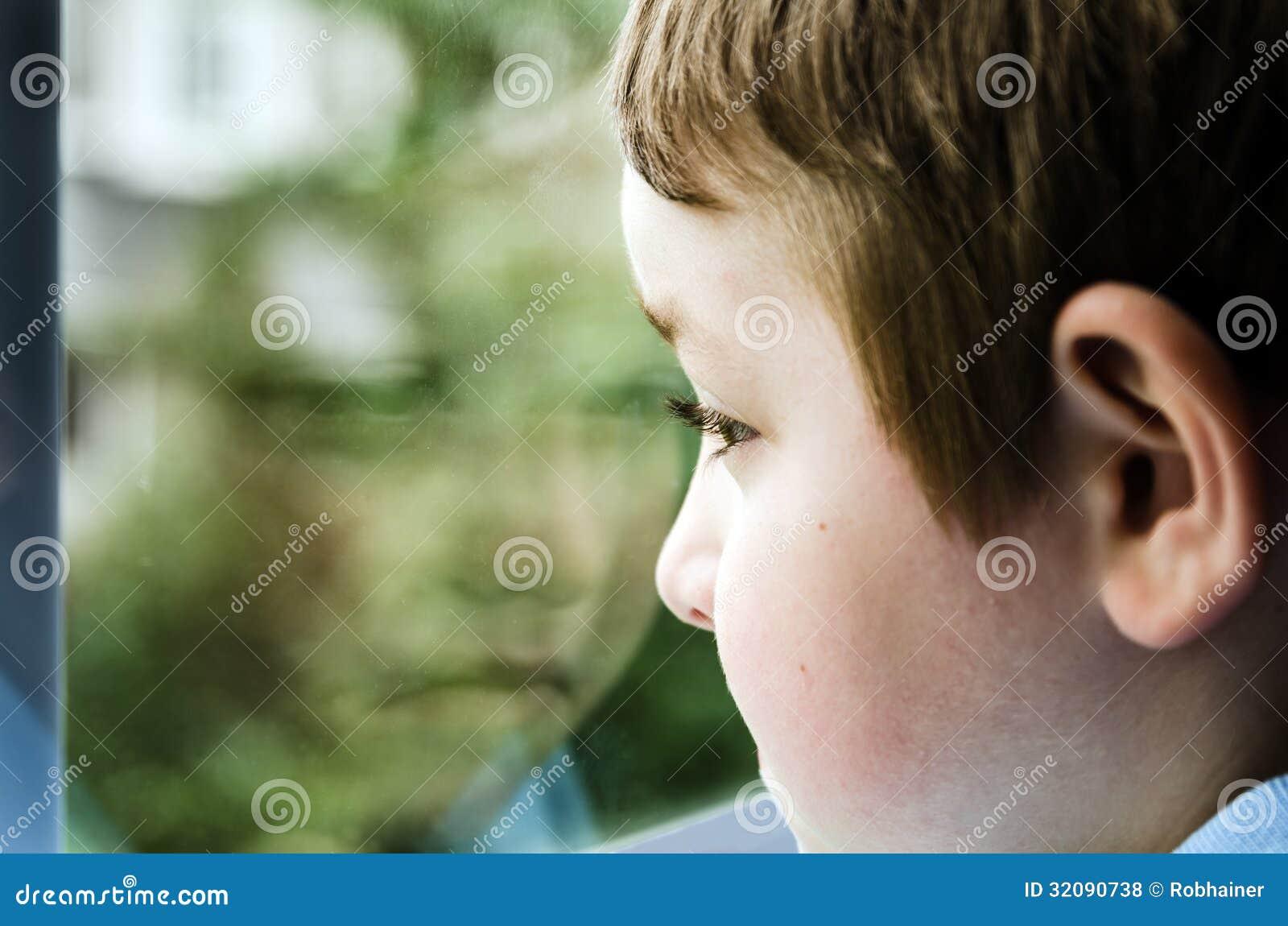 Enfant triste regardant la fenêtre