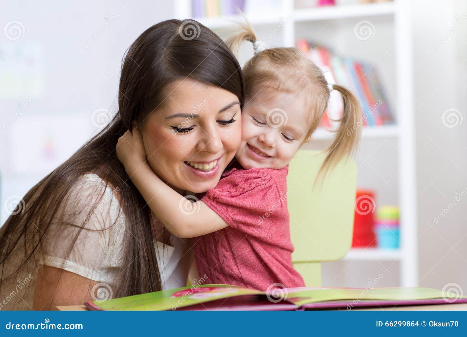 Enfantez embrasser et lire un livre pour badiner à la maison