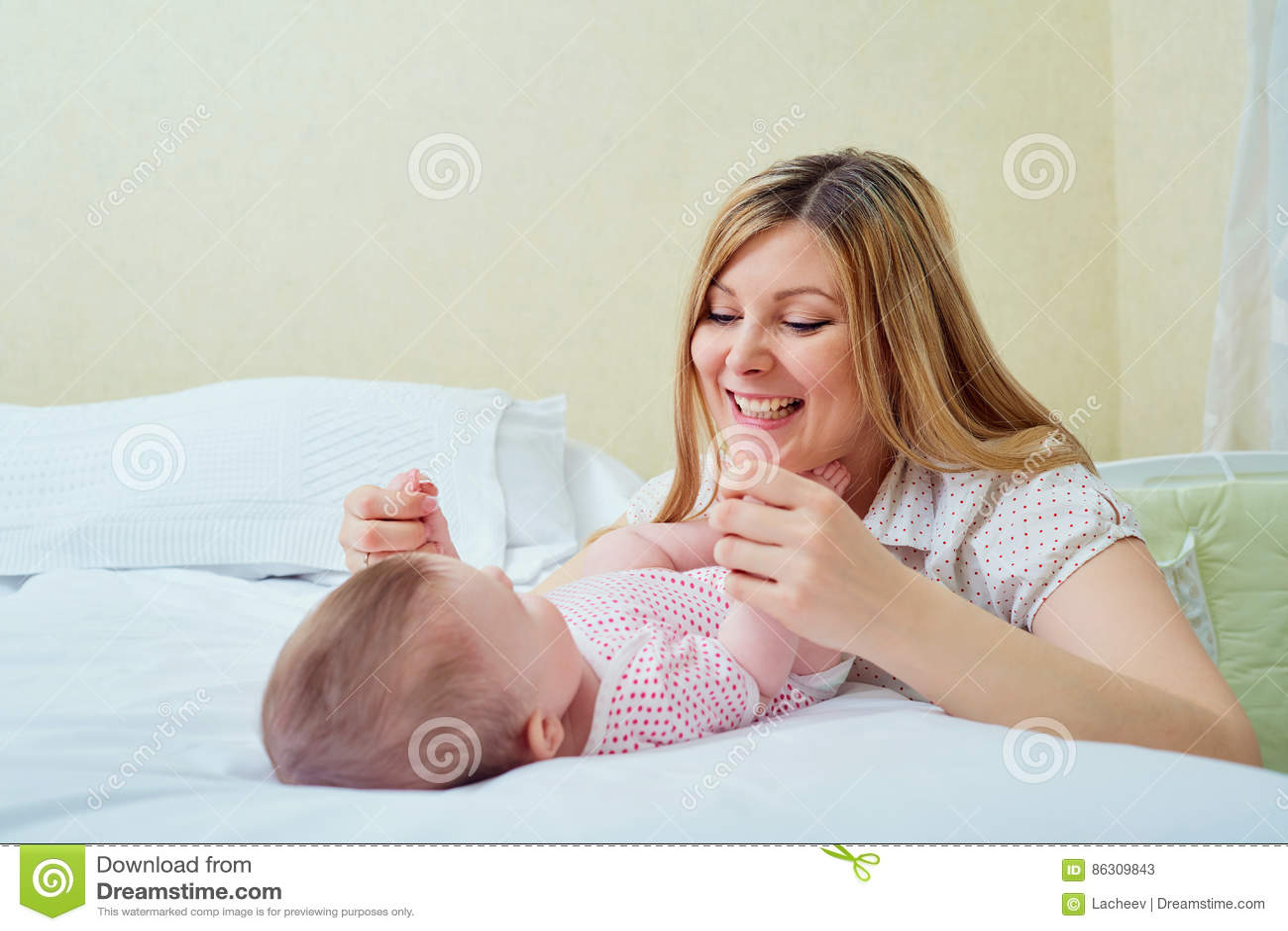 enfantez jouer avec son b b sur le lit la maman sourit son enfant image stock image du. Black Bedroom Furniture Sets. Home Design Ideas