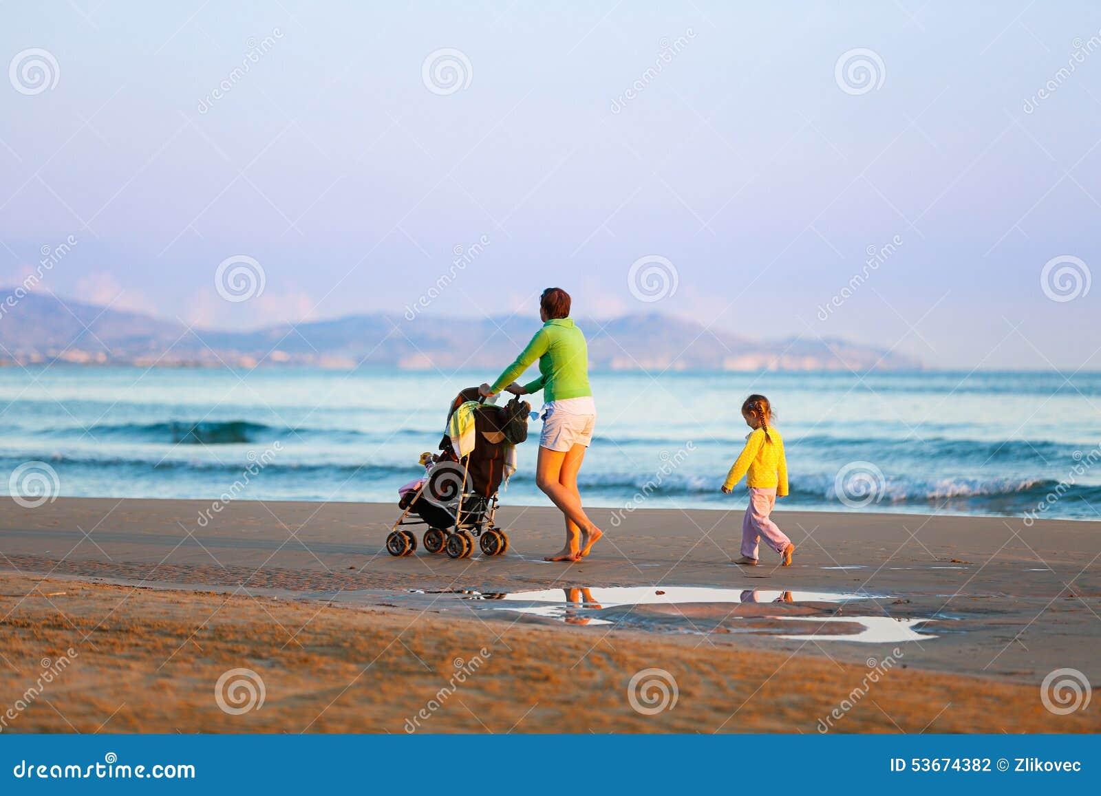 Enfantez la marche sur la plage avec sa fille et bébé