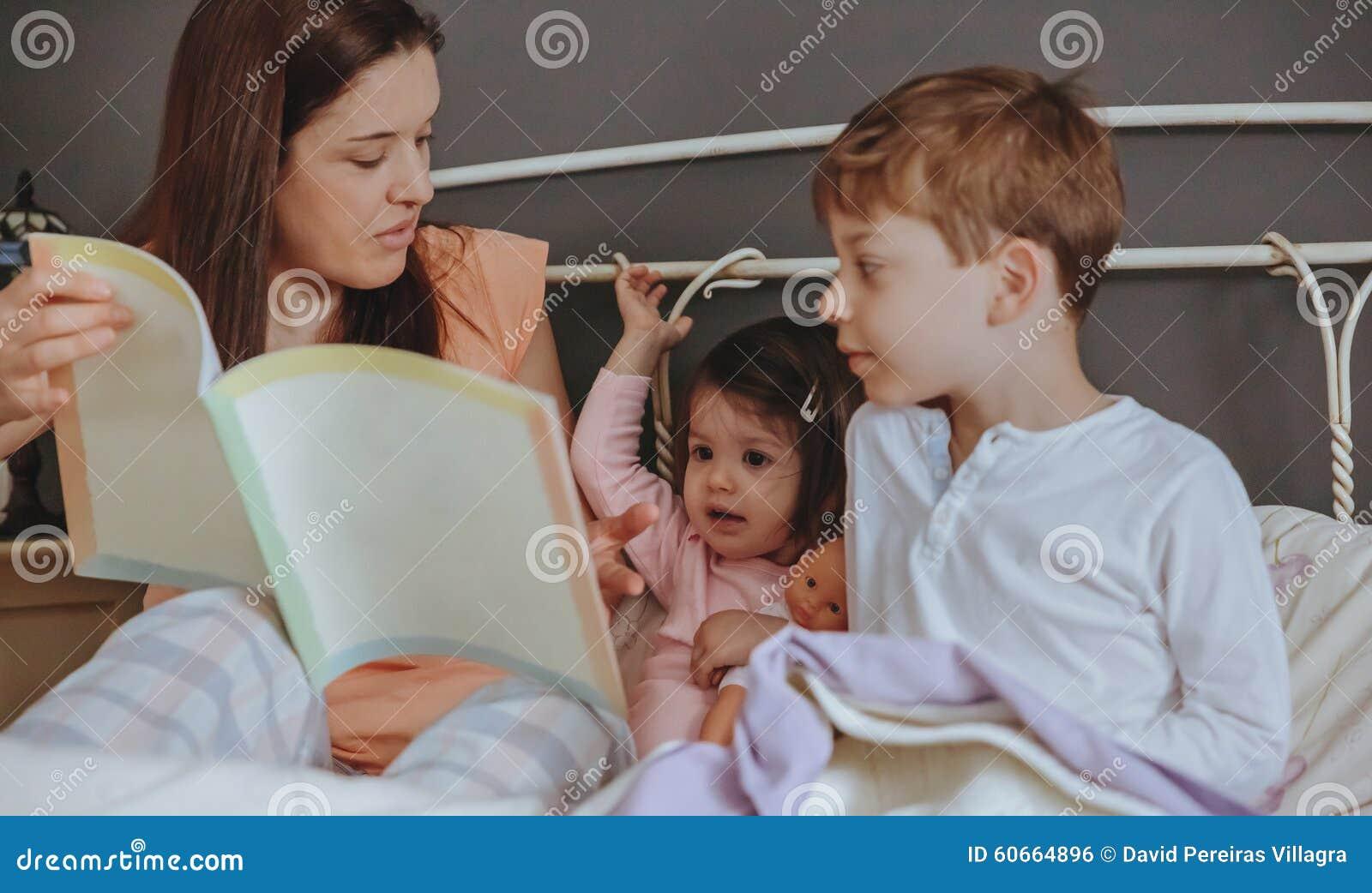 Enfantez le livre de lecture à ses fils dans le lit