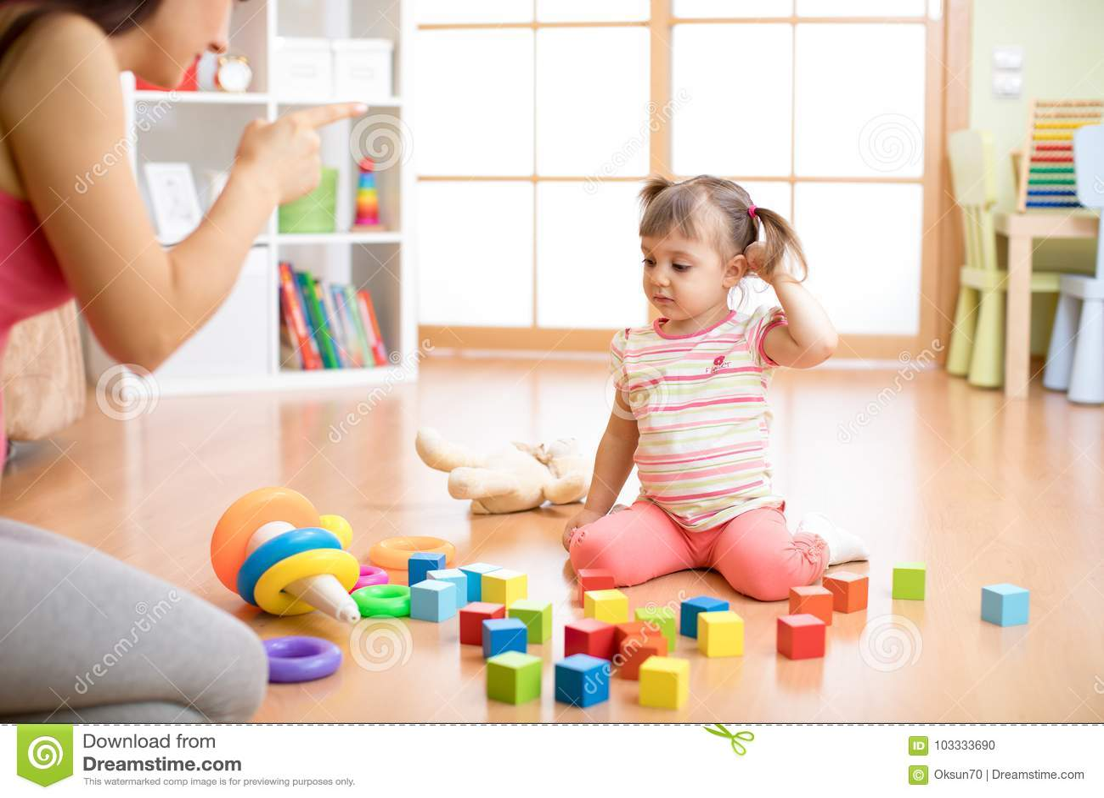Enfantez voient sa fille jouer haut malpropre de jouets la sensation de salon fâchée et critiquer la fille d enfant de tristesse