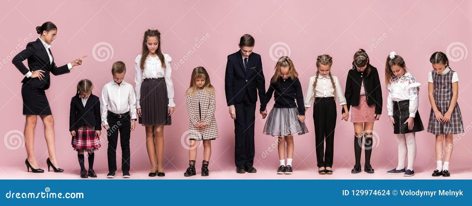 Enfants élégants mignons sur le fond rose de studio Les beaux filles et garçon de l adolescence se tenant ensemble