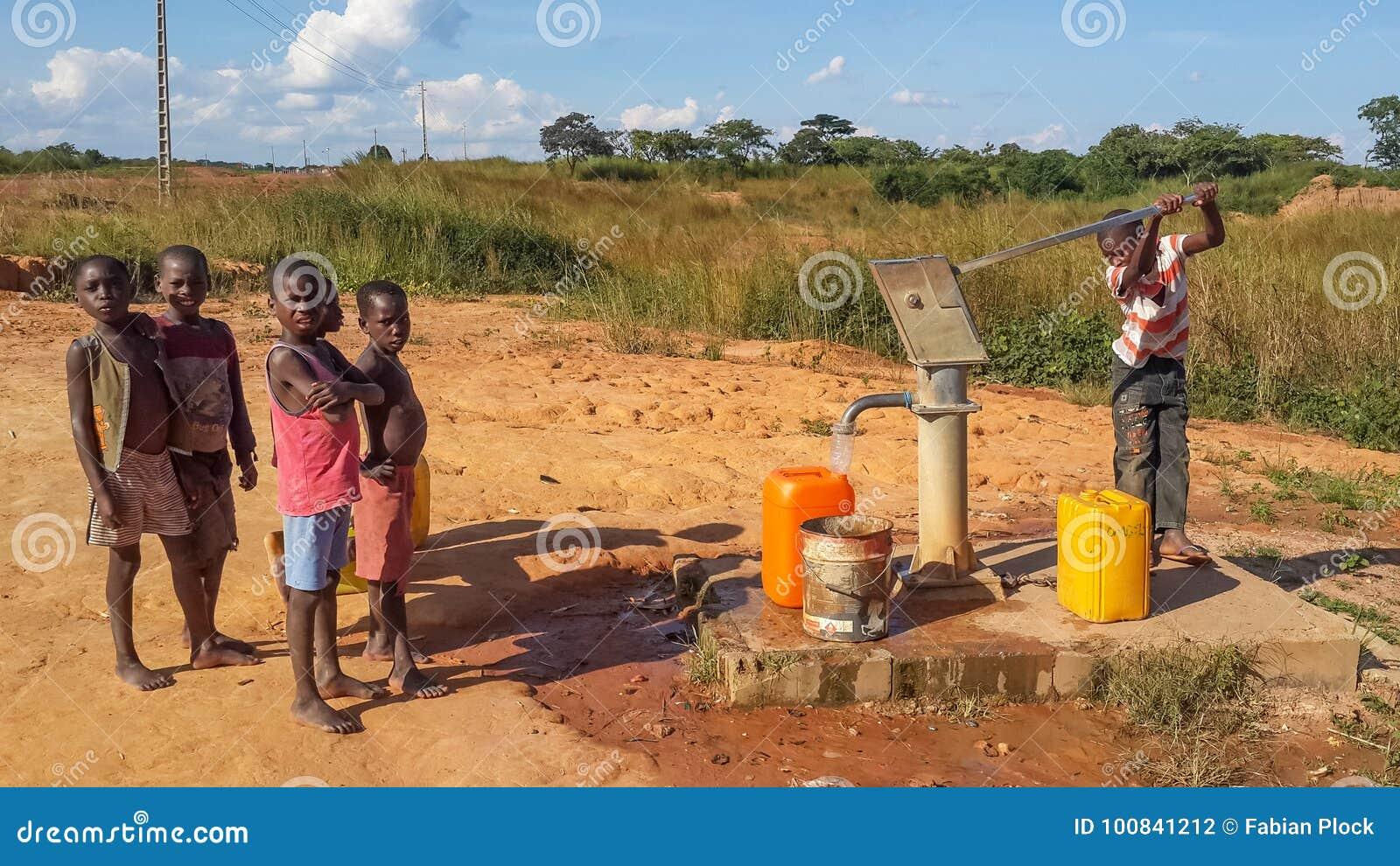 Enfants africains locaux pompant l eau potable bien à construire par c