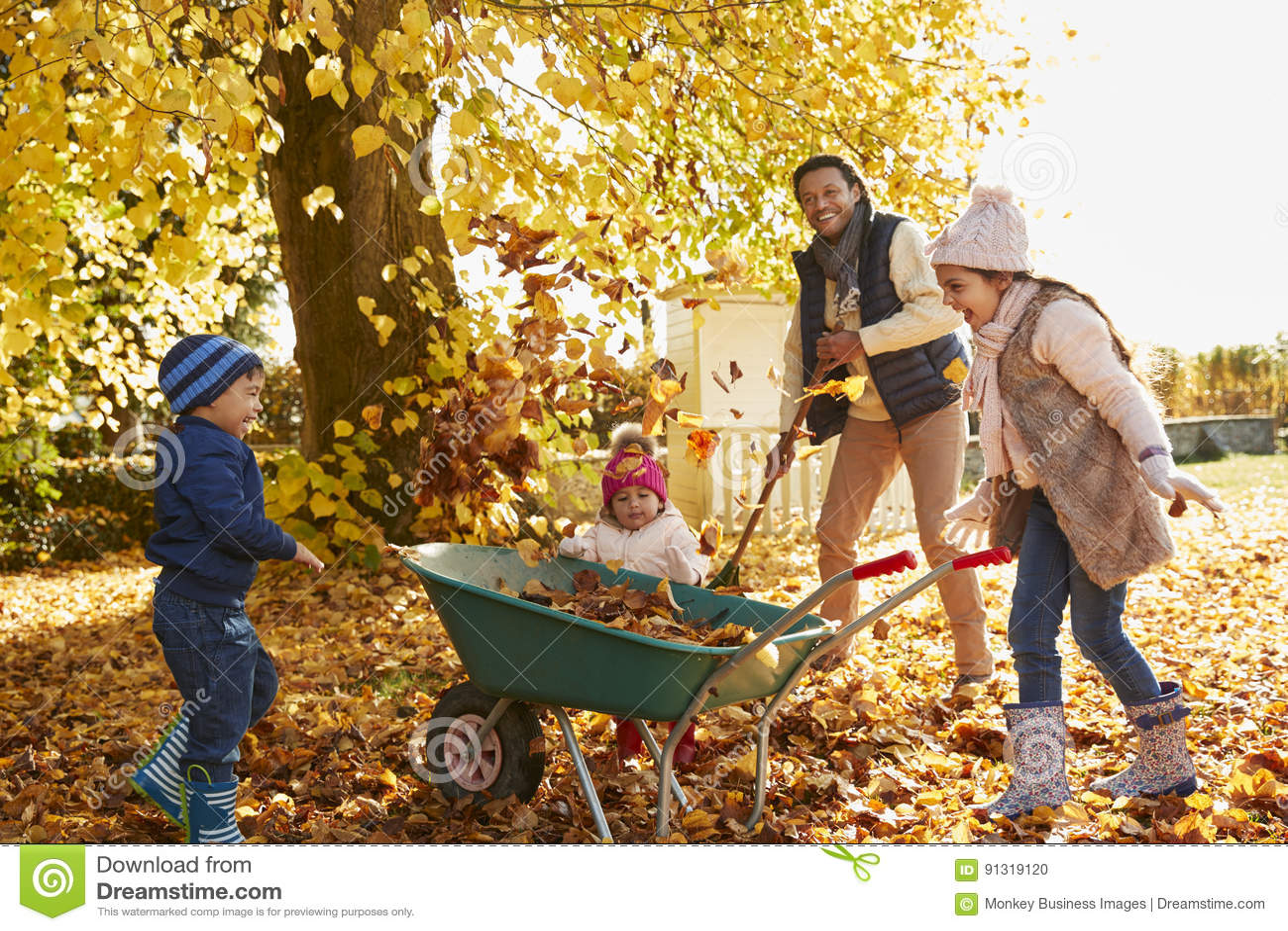 Enfants aidant le père To Collect Autumn Leaves In Garden