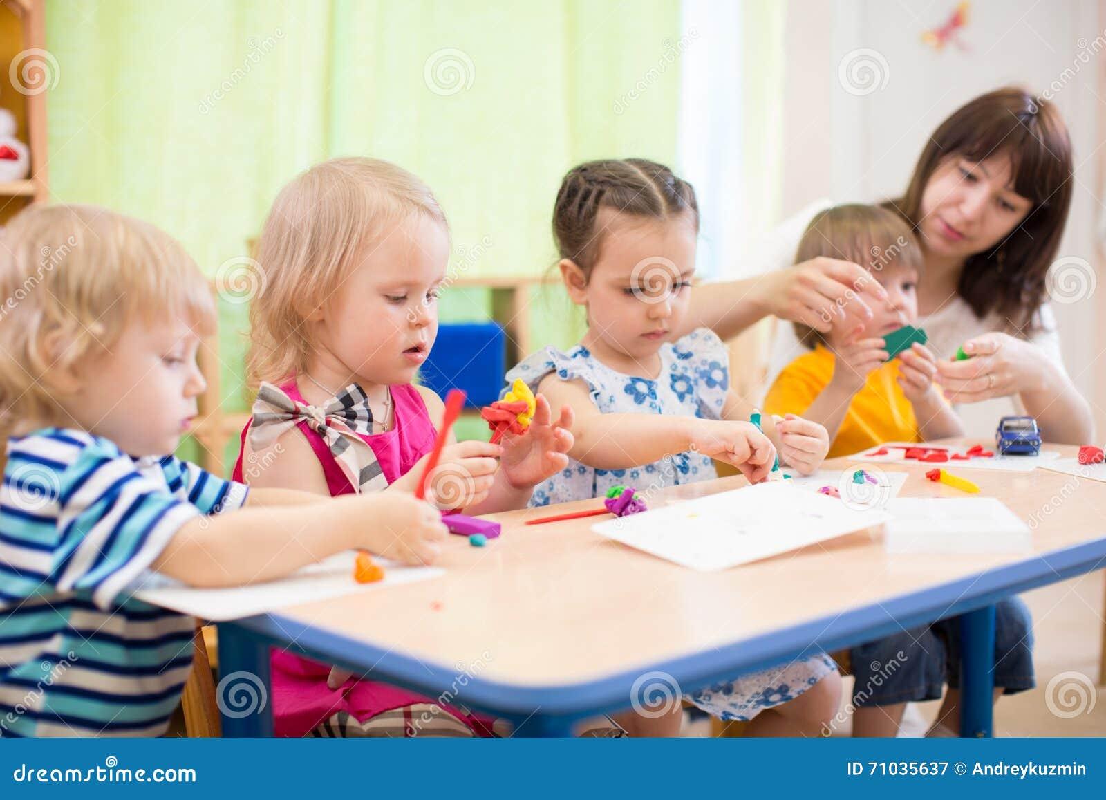 Enfants apprenant des arts et des métiers dans le jardin d enfants avec le professeur