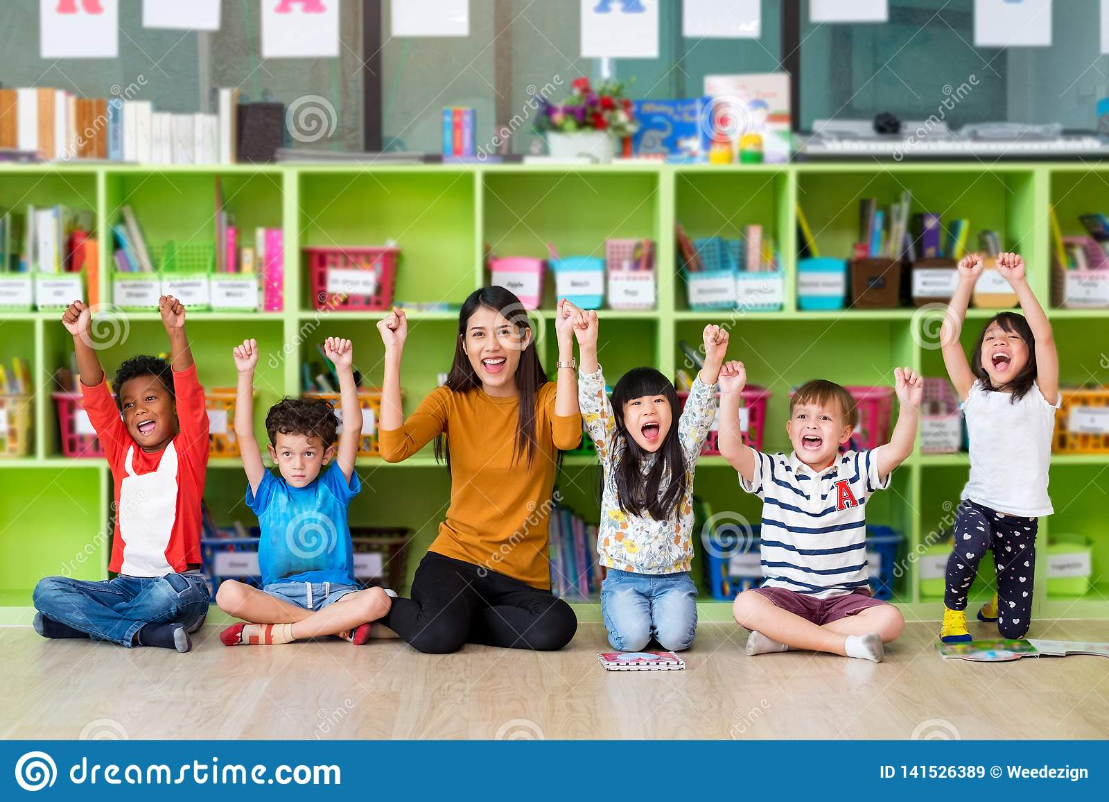 Enfants asiatiques heureux de professeur féminin et de métis dans la salle de classe, concept d école de jardin d enfants pré
