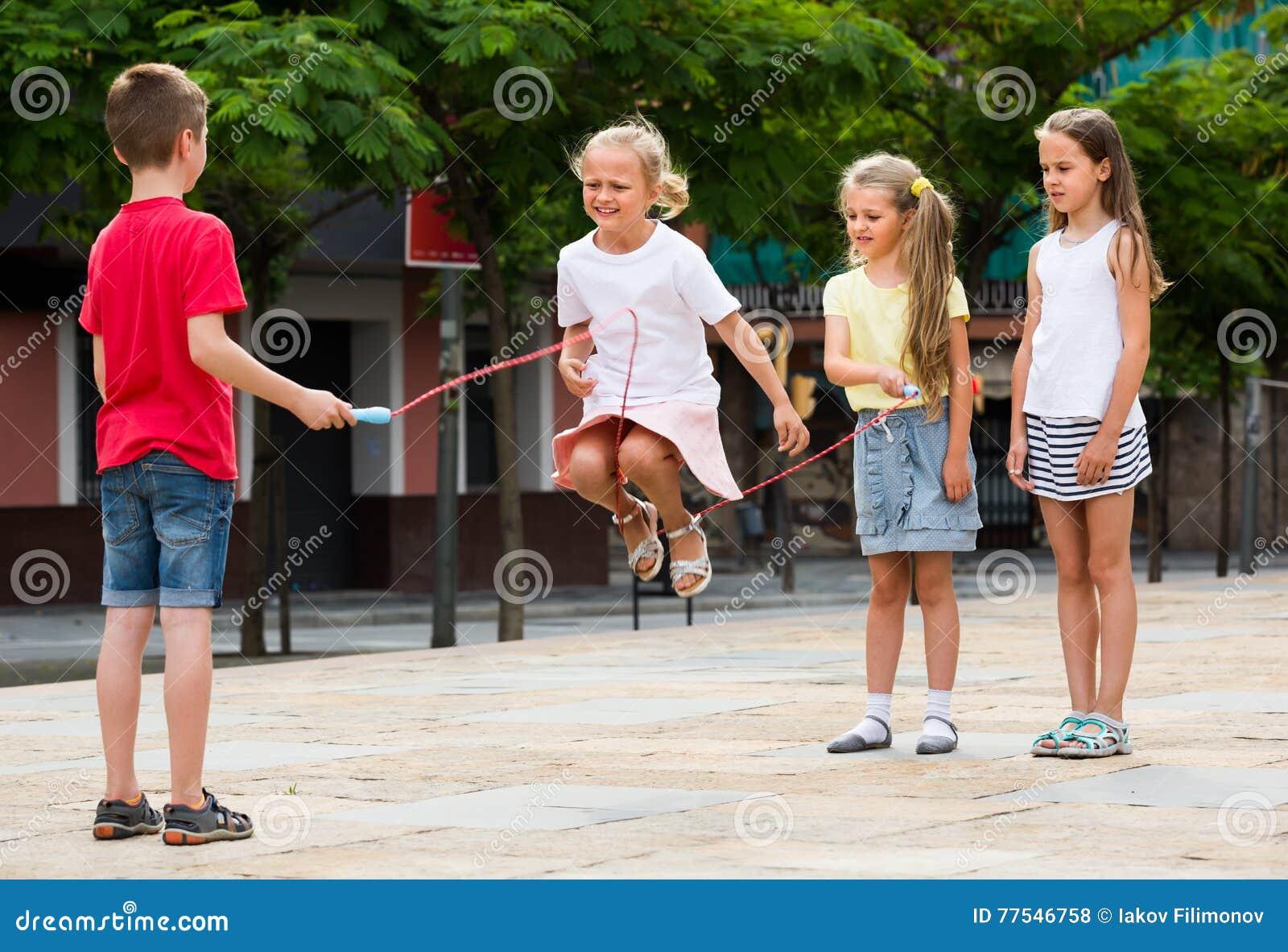 enfants avec la corde sauter au terrain de jeu photo stock image du jardin lifestyle 77546758. Black Bedroom Furniture Sets. Home Design Ideas