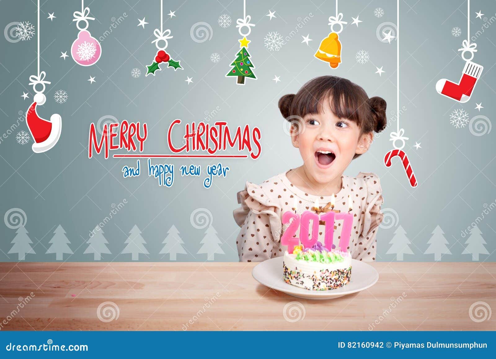 Enfants ayant l amusement à la partie de nouvelle année avec le gâteau et la bougie 2017