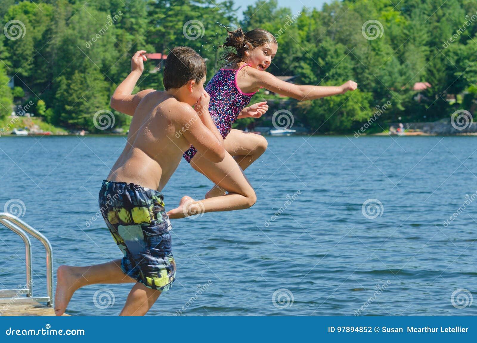 Enfants ayant l amusement d été sautant outre du dock dans le lac