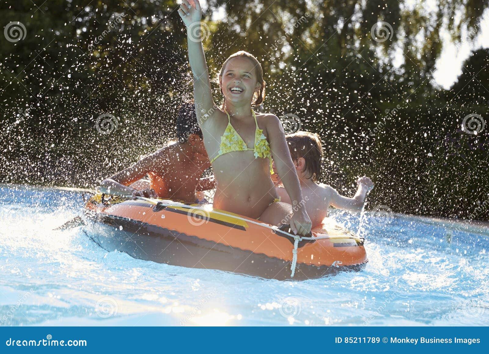 Enfants ayant l amusement sur gonflable dans la piscine extérieure